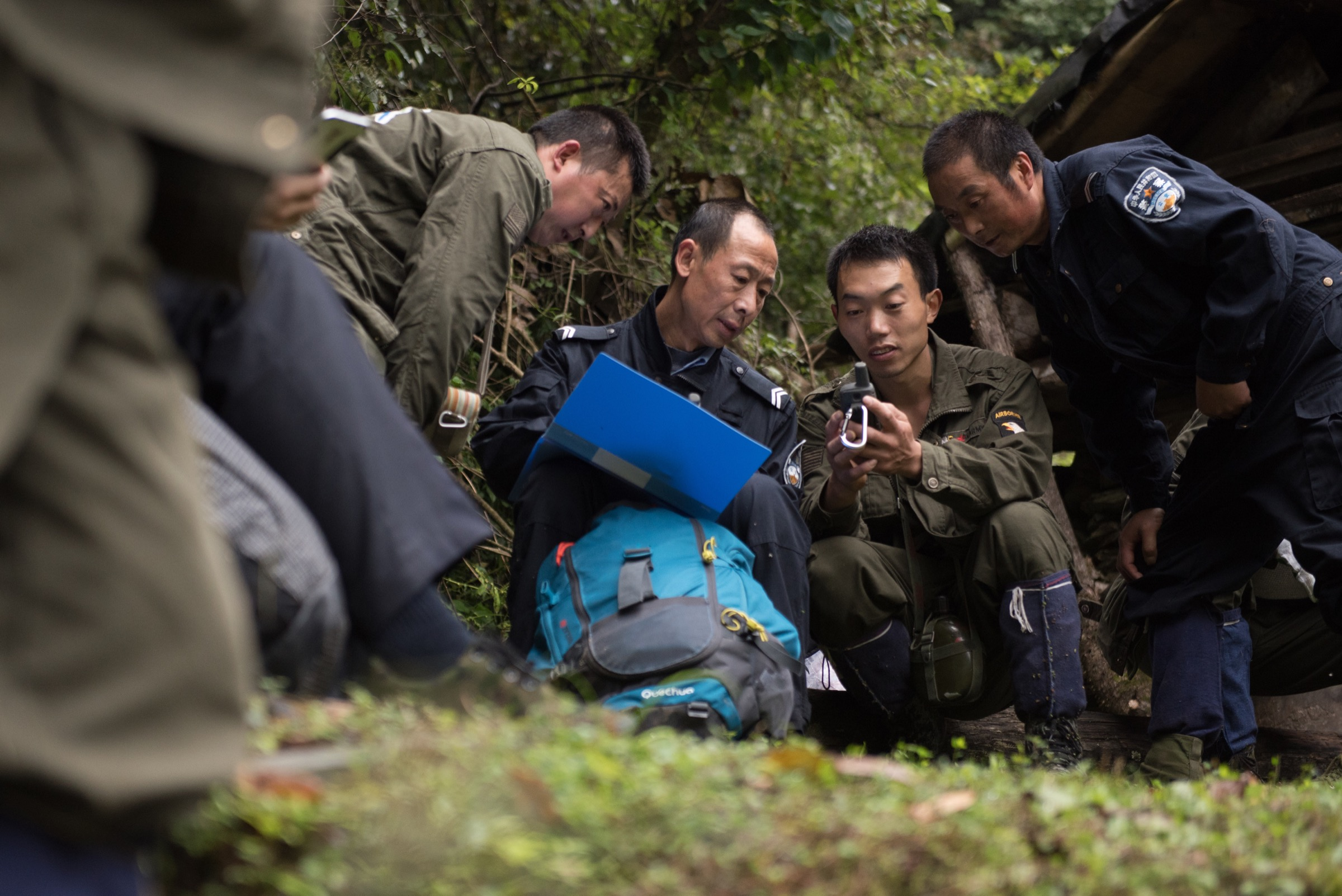 Meng Ji checks GPS coordinates of their route with other patrol members and two local Sichuan government forestry department officers. Photograph by Kyle Obermann
