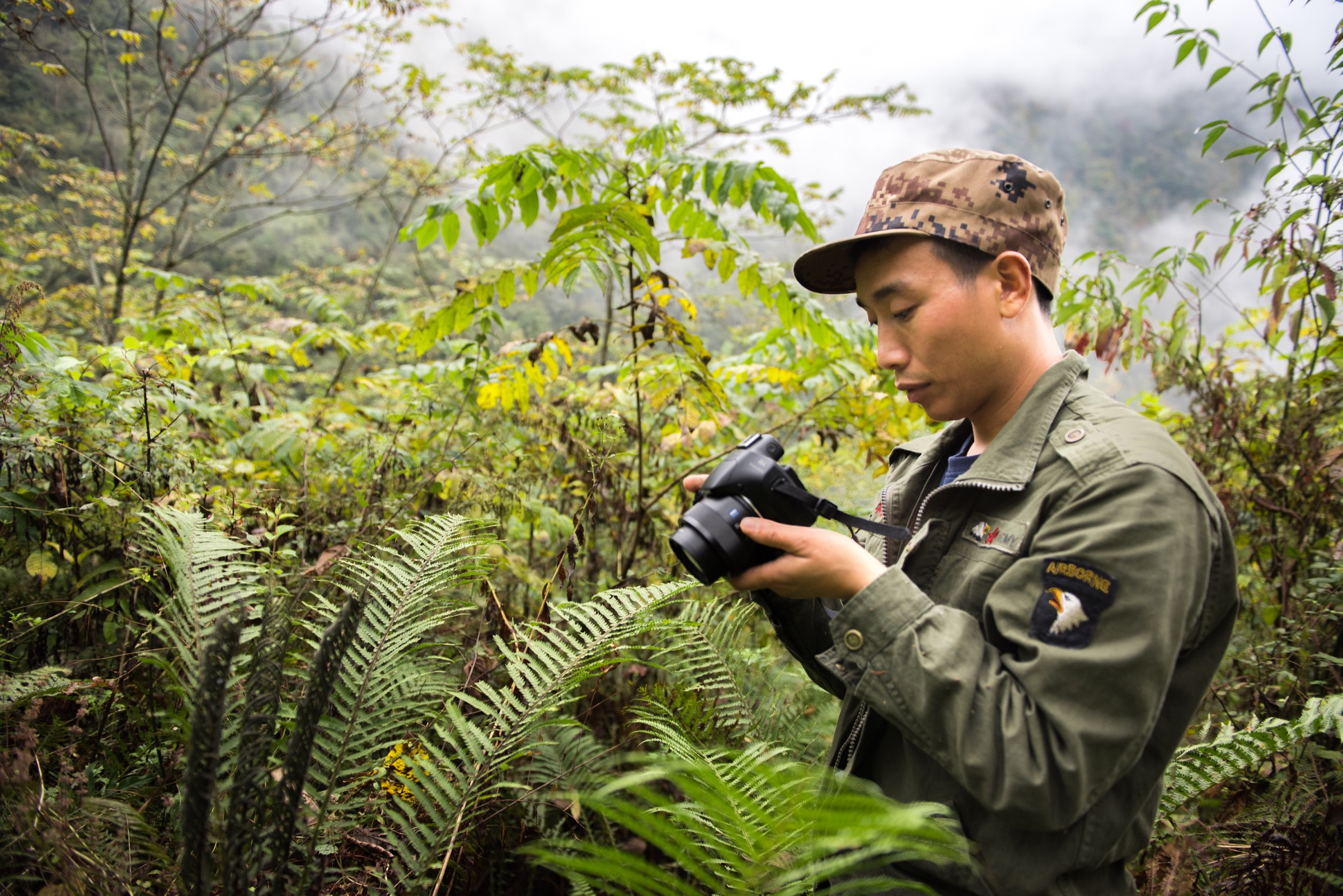 Li Xinrui, a member of Guanba Community Reserve's patrol team, is in charge of photographing species encountered during the team's patrol of Guanba Valley. Photograph by Kyle Obermann