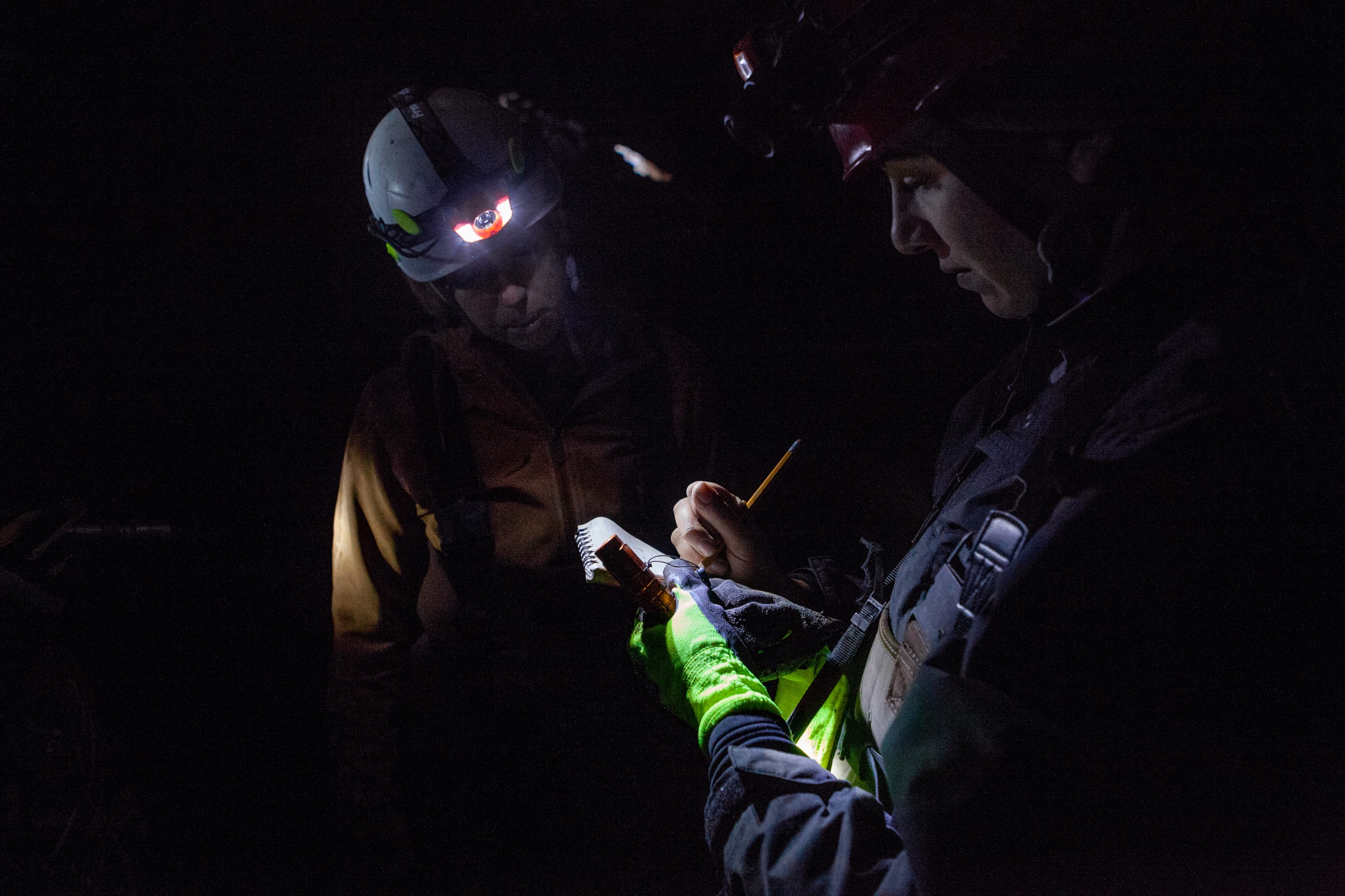 Mandy Bailey (left) and Kate Ritzko (right) of the New York State Department of Environmental Conservation record the number and species of bats that they see during the survey of a cave in Upstate New York.