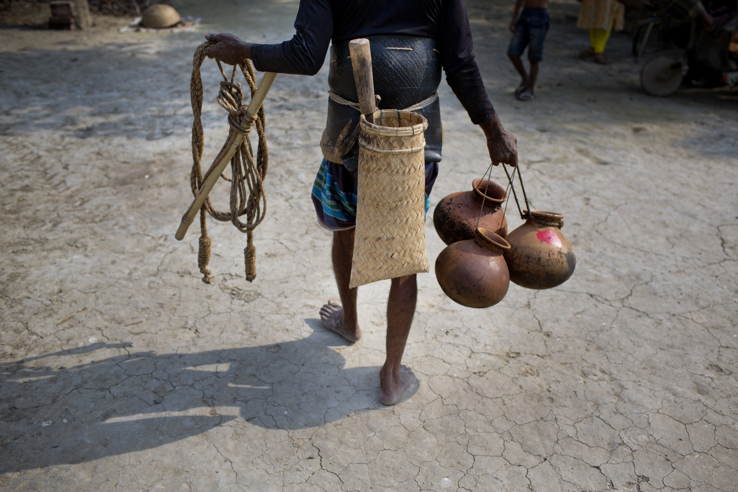 With his tools of the trade, a <em>gachhi</em> goes off to climb and tap date palm trees for the sap that he hopes to sell to excited locals the very next day. Photograph by A.M. Ahad