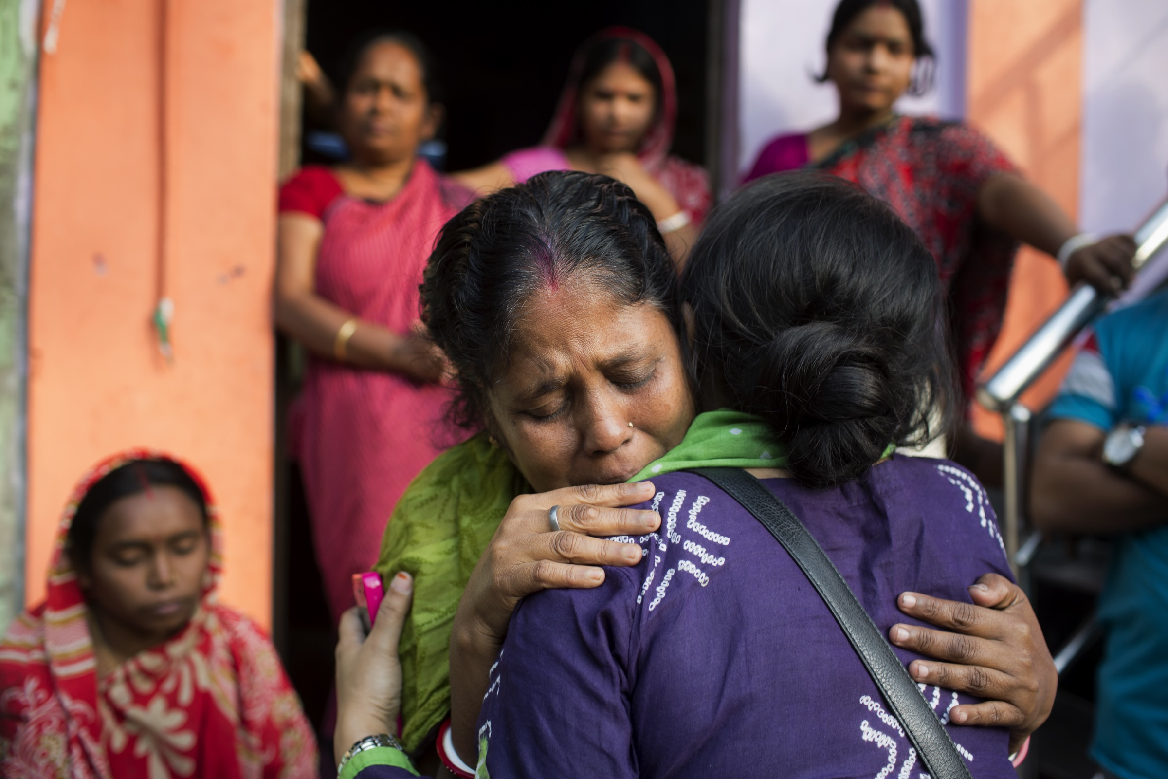 Arifa Nazneen (in purple), a senior medical officer at ICDDR,B is frequently on the front lines of Nipah investigations. Here she tries to comfort a mother in Faridpur whose son who fell ill after drinking date palm sap during a gathering to celebrate his graduation from high school. He has since died. Photograph by A.M. Ahad