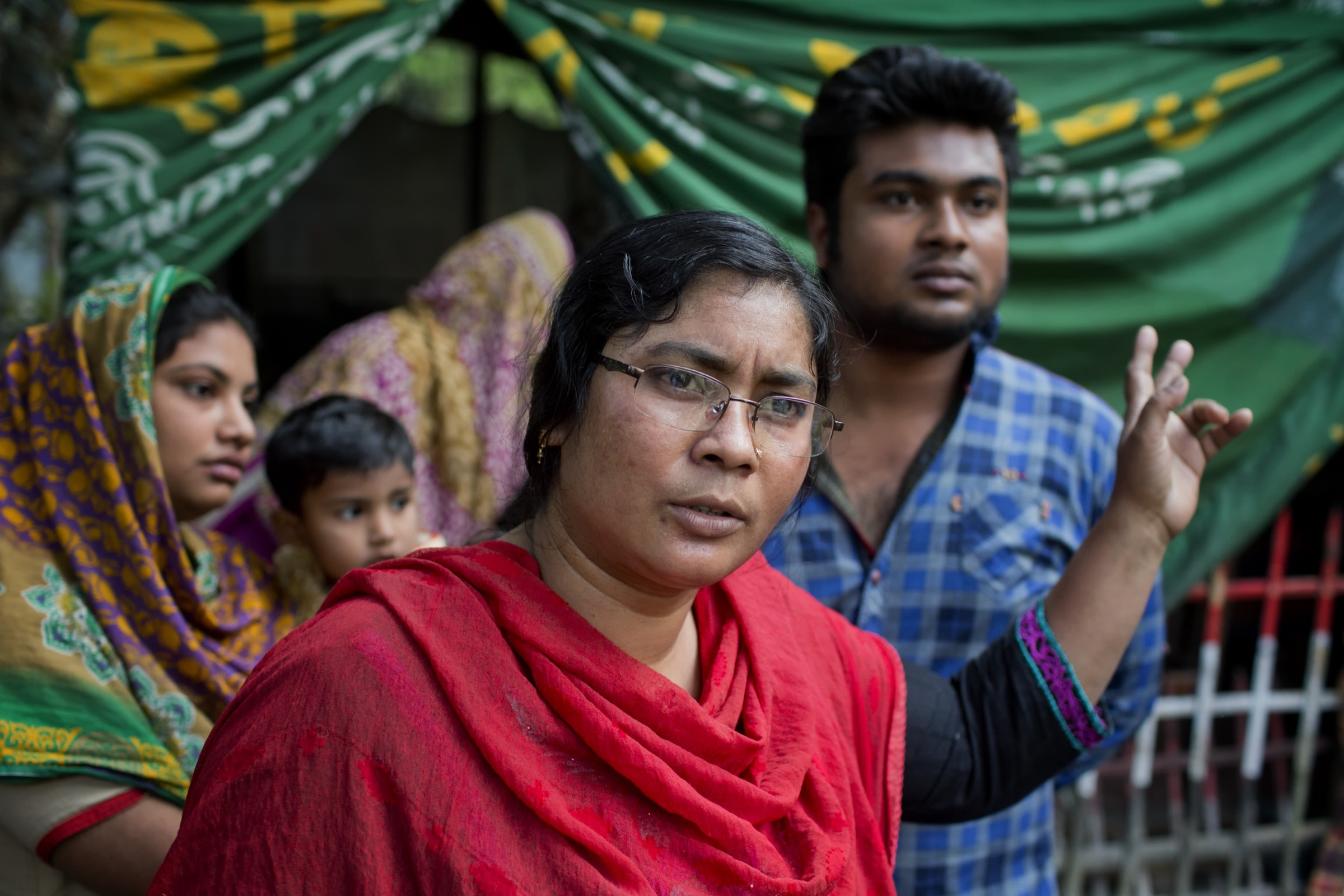 A woman discusses the 2011 Nipah outbreak in Faridpur that took seven members of her family. She and her son (in blue) were also infected but survived. Photograph by A.M. Ahad