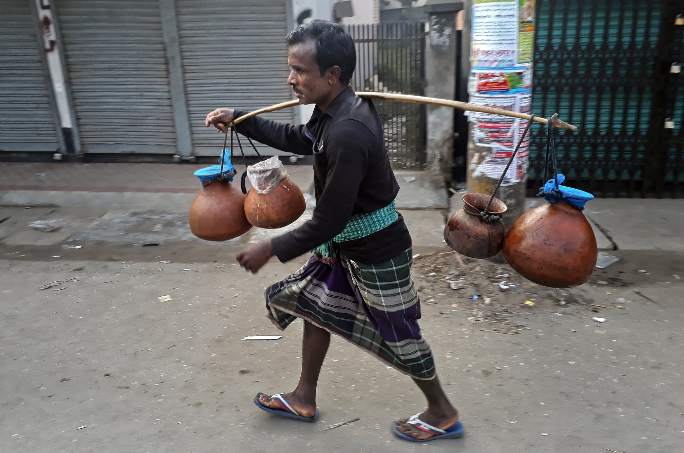A gachhi walks the streets of Rangpur City carrying pots filled with sap collected from date palm trees (<em>Phoenix dactylifera</em>), a delicacy in this part of Bangladesh. Photograph by A.M. Ahad