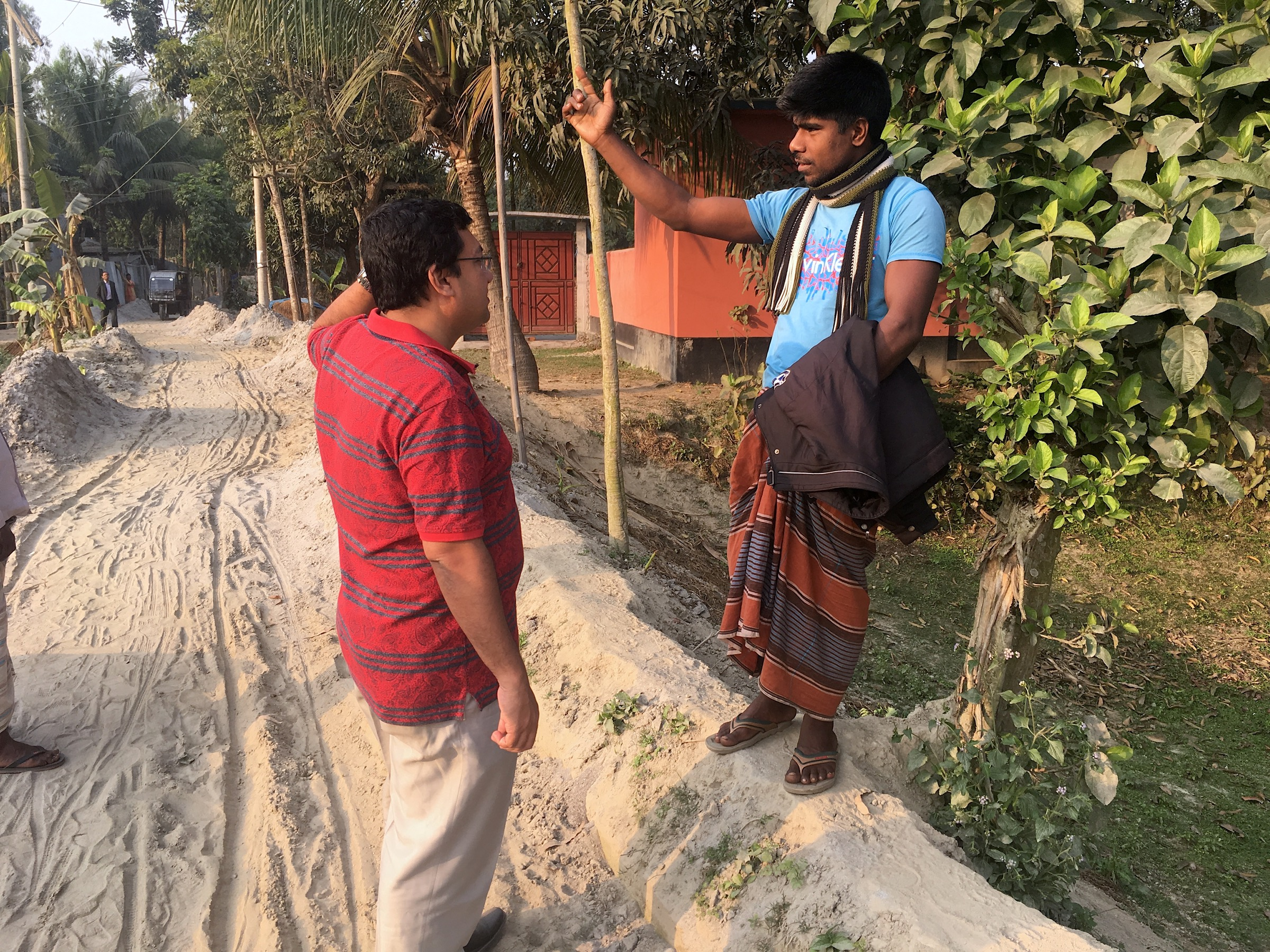 Physician Hossain M. S. Sazzad from ICDDR,B asks a resident of the village of Mohonpur for directions to the home of the local <em>gachhi</em>, a collector and seller of date palm sap. Photograph by Steven Bedard