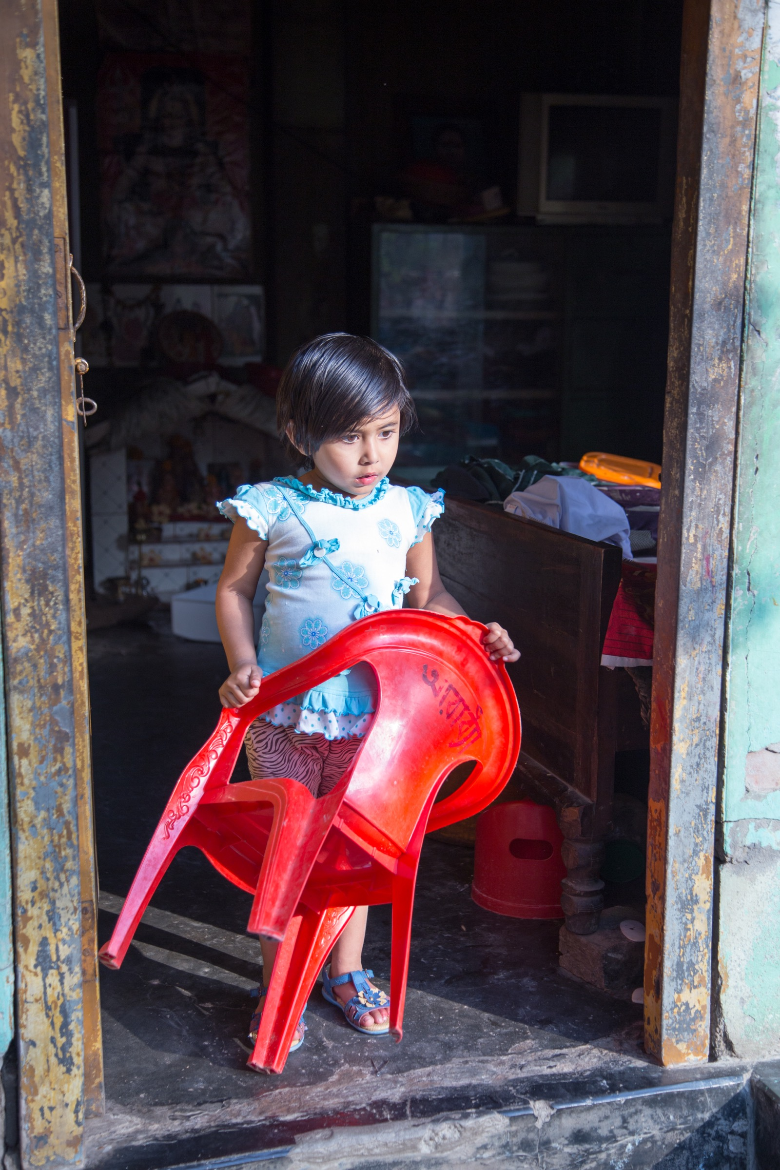 A young girl has already started practicing the customary greeting in in northern Bangladesh, offering visitors with a comfortable place to sit. Photograph by Steven Bedard