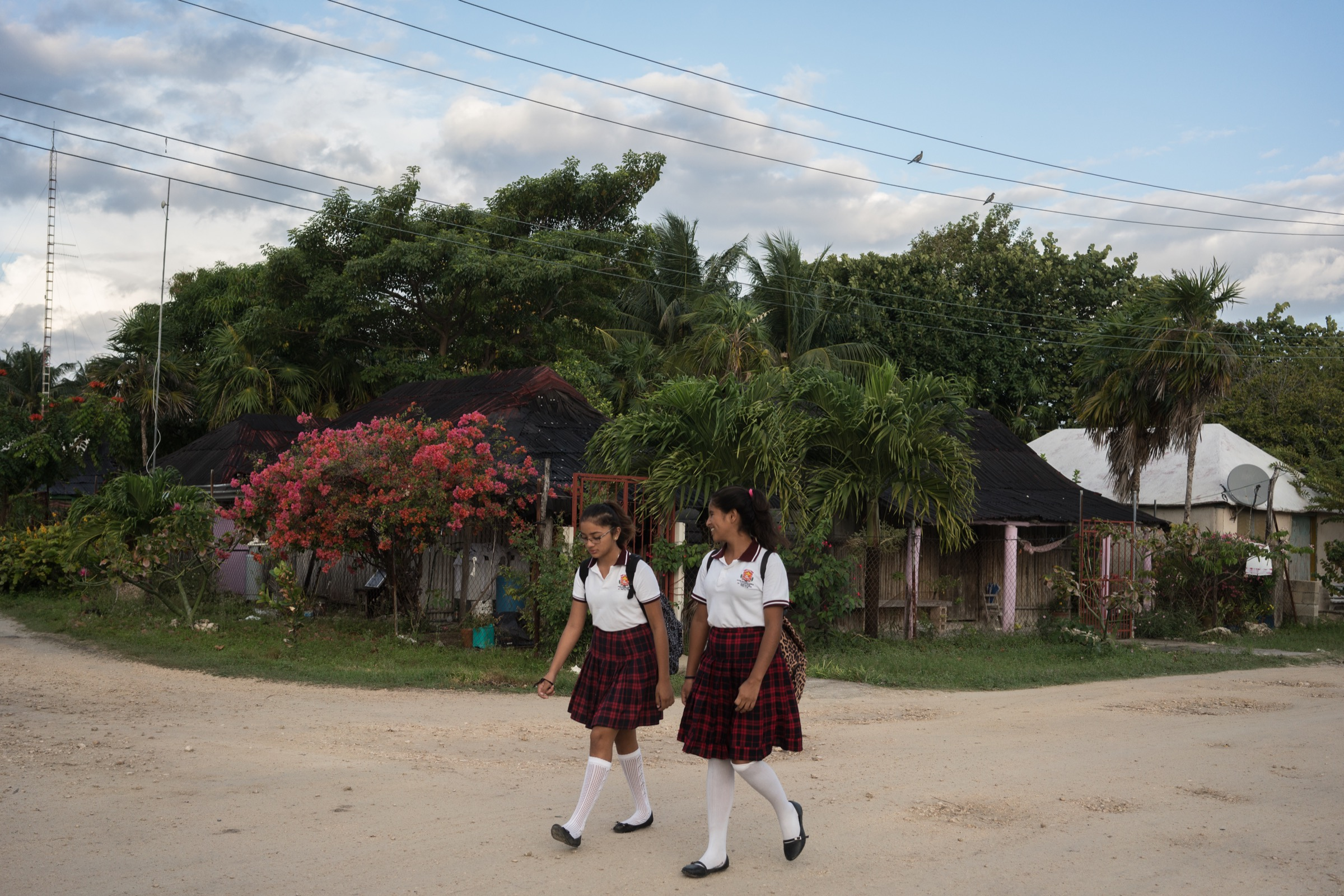 Two girls walk to school in Punta Allen, Mexico, a town that has prospered because of its successful lobster fishery. Photograph by Dominic Bracco II