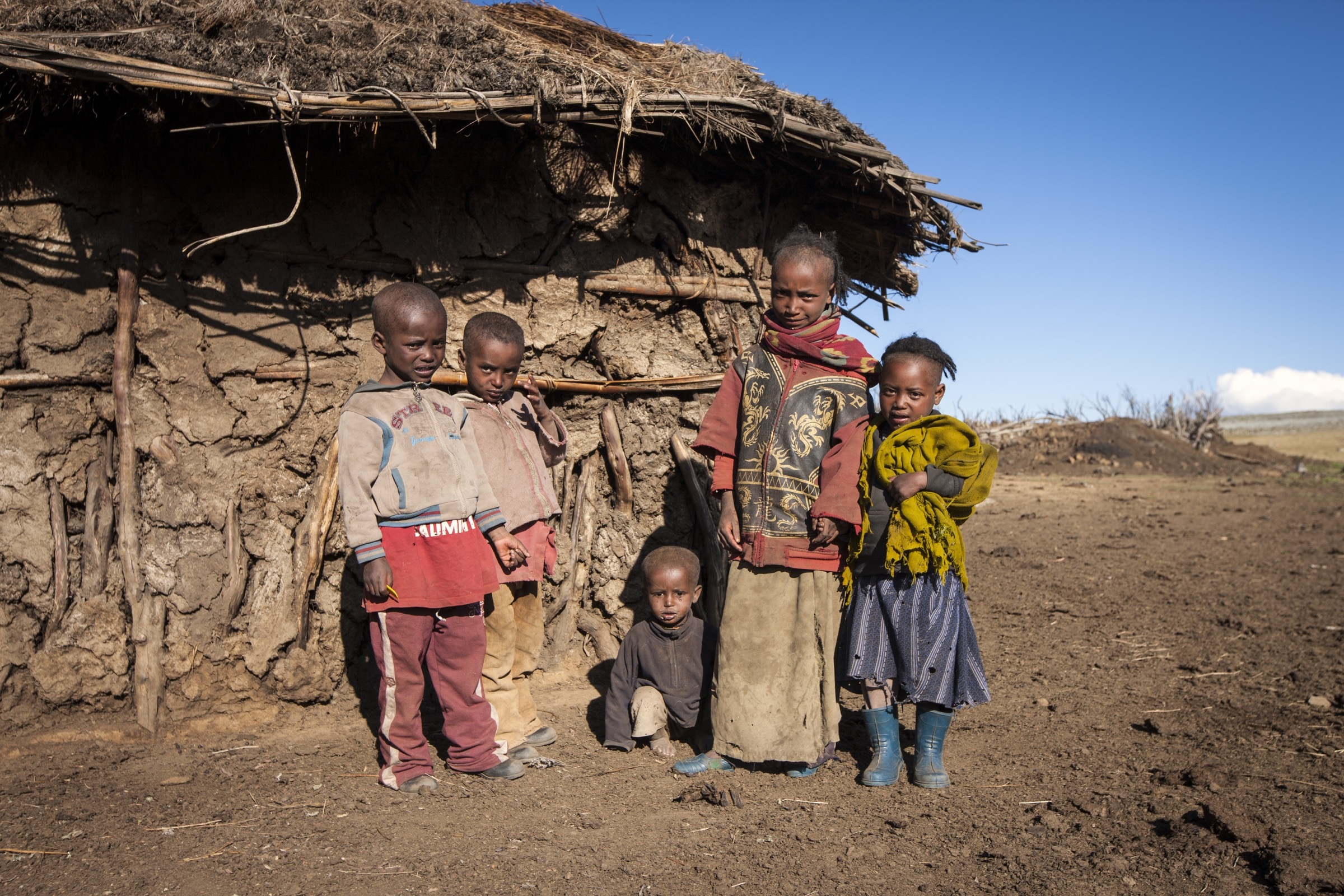 A group of inquisitive children stands outside of a mud hut in the Bale Mountains of Ethiopia.