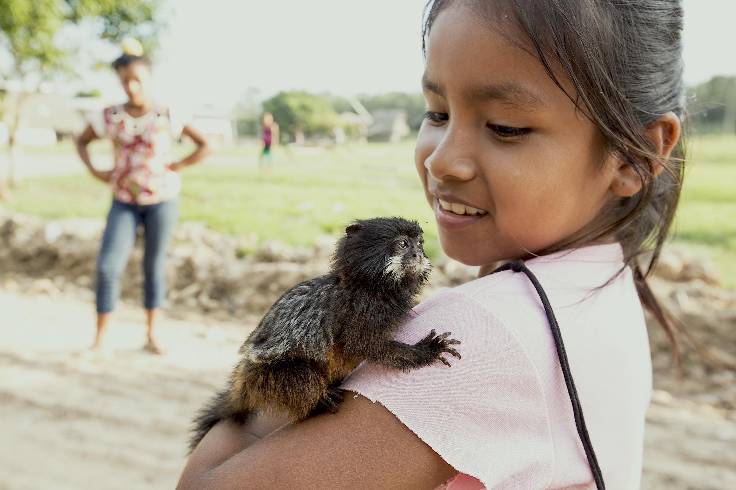 A young girl in Pueblo Libre proudly shows off her pet monkey.