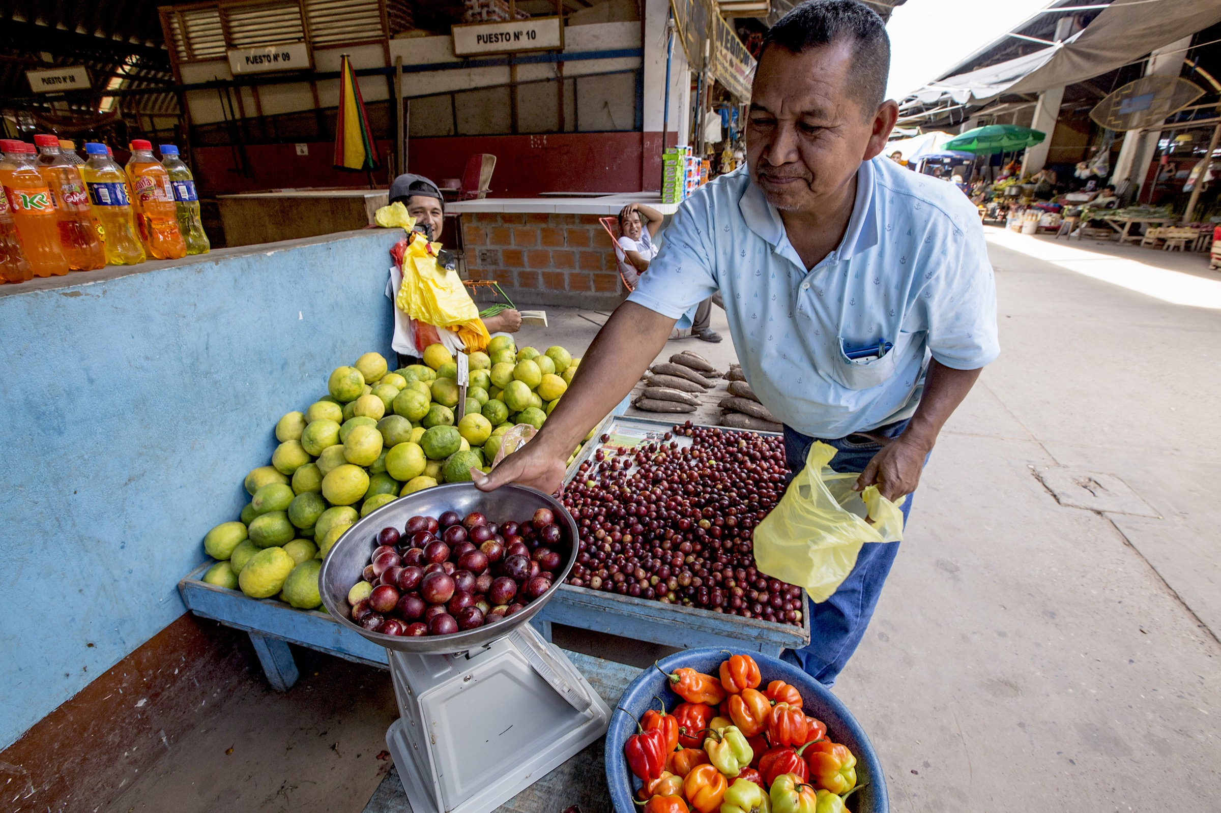 A seller at a local market weighs a batch of camu camu, a plum-like fruit that is becoming increasingly popular in Lima's restaurant scene.