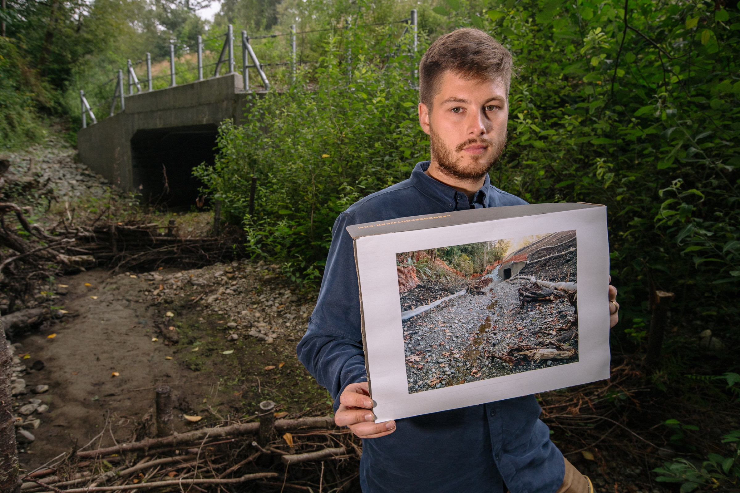 Biologist David Bailey stands in a streambed holding a photograph of the same waterway prior to the Tulalip team's construction of beaver dam analogues, a step toward making the area more suitable for relocated beavers.