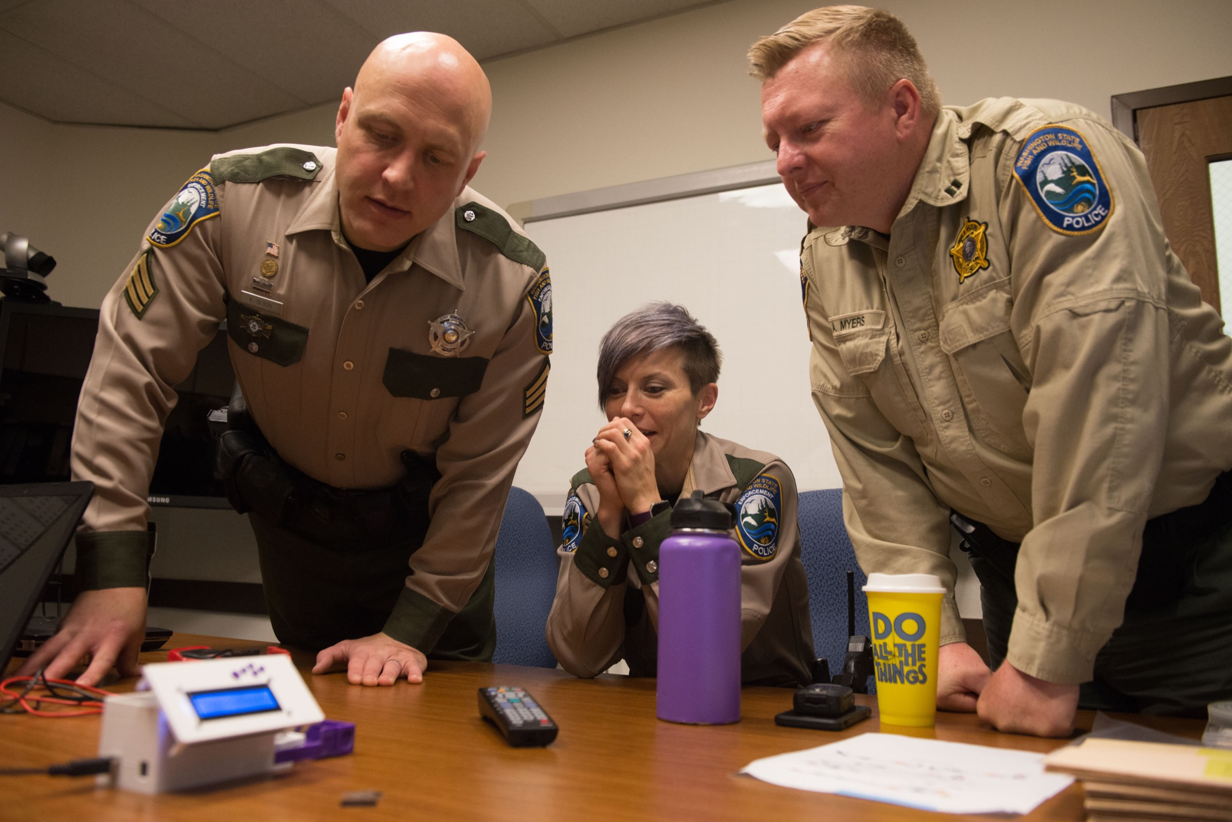 Sergeant Erik Olson, Officer Tylar Stephenson and Captain Alan Myers inspect the DNA barcode scanner during a test run. Photograph by Daniel Berman