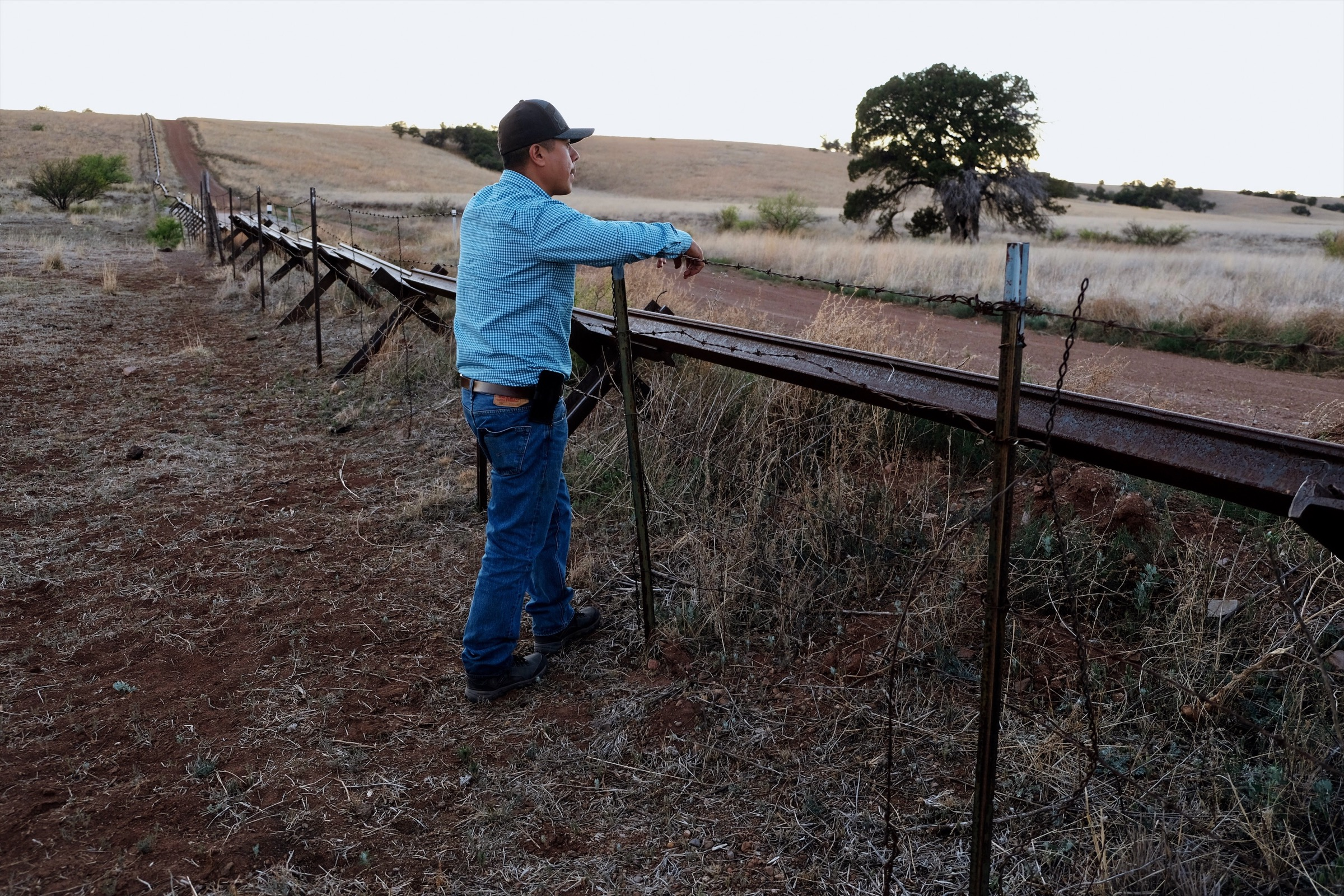 Daniel Toyo, an agricultural technician for the environmental non-profit Naturalia looks into Arizona across a fence that marks the northern boundary of the group's Rancho Los Fresnos property. Photograph by Julian Smith