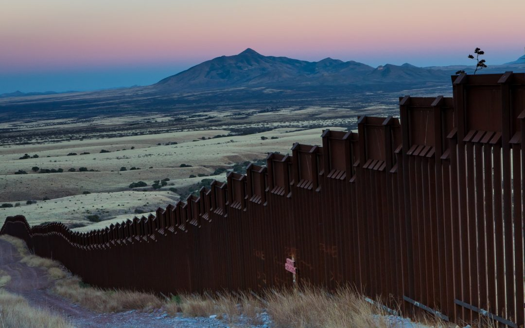 This section of border wall, originally constructed in 2008, stretches from the west bank of the San Pedro River into the foothills of the Huachuca Mountains in Arizona, a critical wildlife corridor between Sky Islands like the one visible in the background, in Sonora, Mexico. Photograph by Krista Schyler