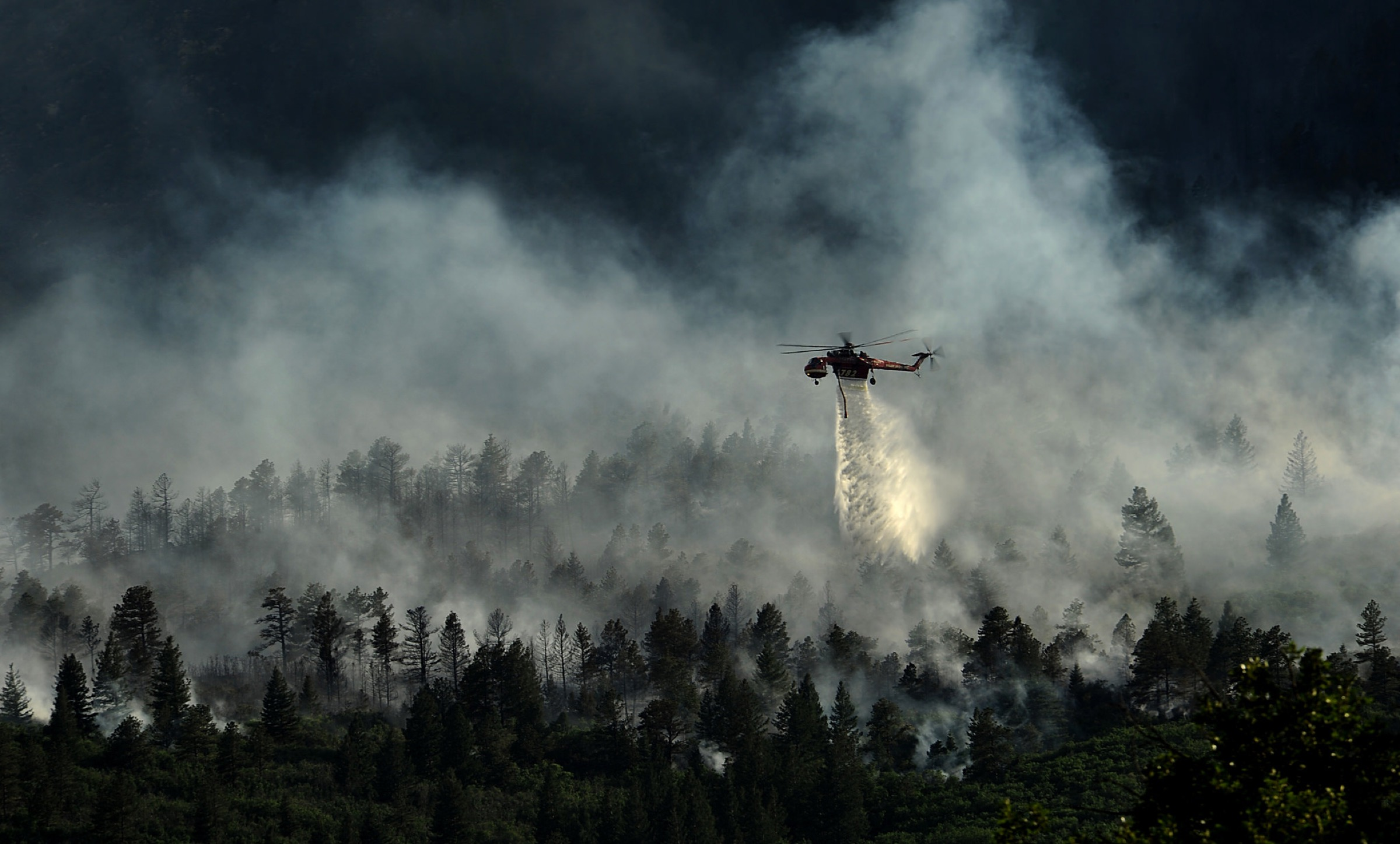 A helicopter drops water on the fire as firefighters continued to battle the blaze that burned into the evening hours in Waldo Canyon on the U.S. Air Force Academy near Colorado Springs on June 27, 2012. Photograph by Master Sgt. Jeremy Lock / U.S. Air Force (Released)