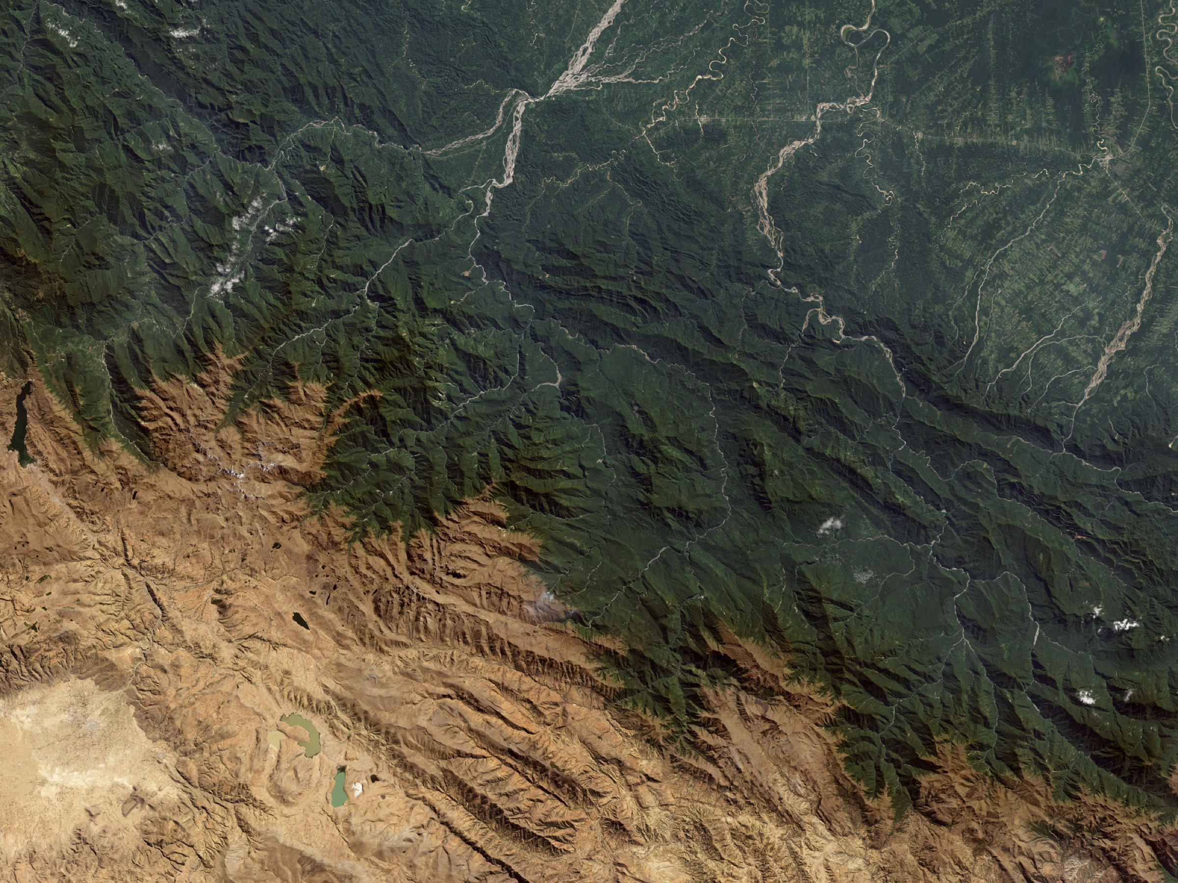 A satellite image of the Andes Mountains showing a wide range of habitats, including those fragmented by agriculture in the upper-right portion of the photo—Photograph by Stocktrek Images/Getty