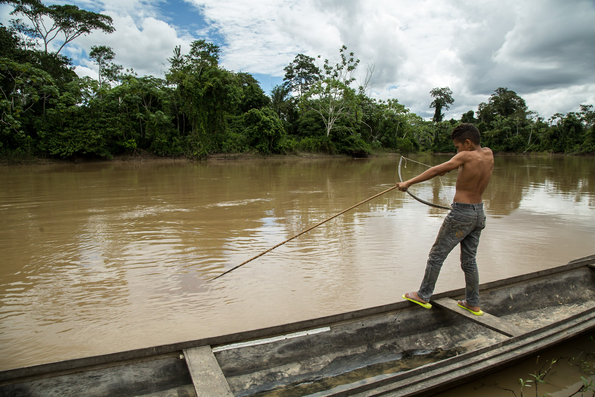A young boy scans the water in search of his next target. A bow and long arrow is the traditional weapon riberinhos use to catch the monster pirarucu (Arapaima gigas), a fish native to Amazon rivers. Local children learn to fish, hunt and navigate flooded forests in dugout canoes almost as soon as they can walk.