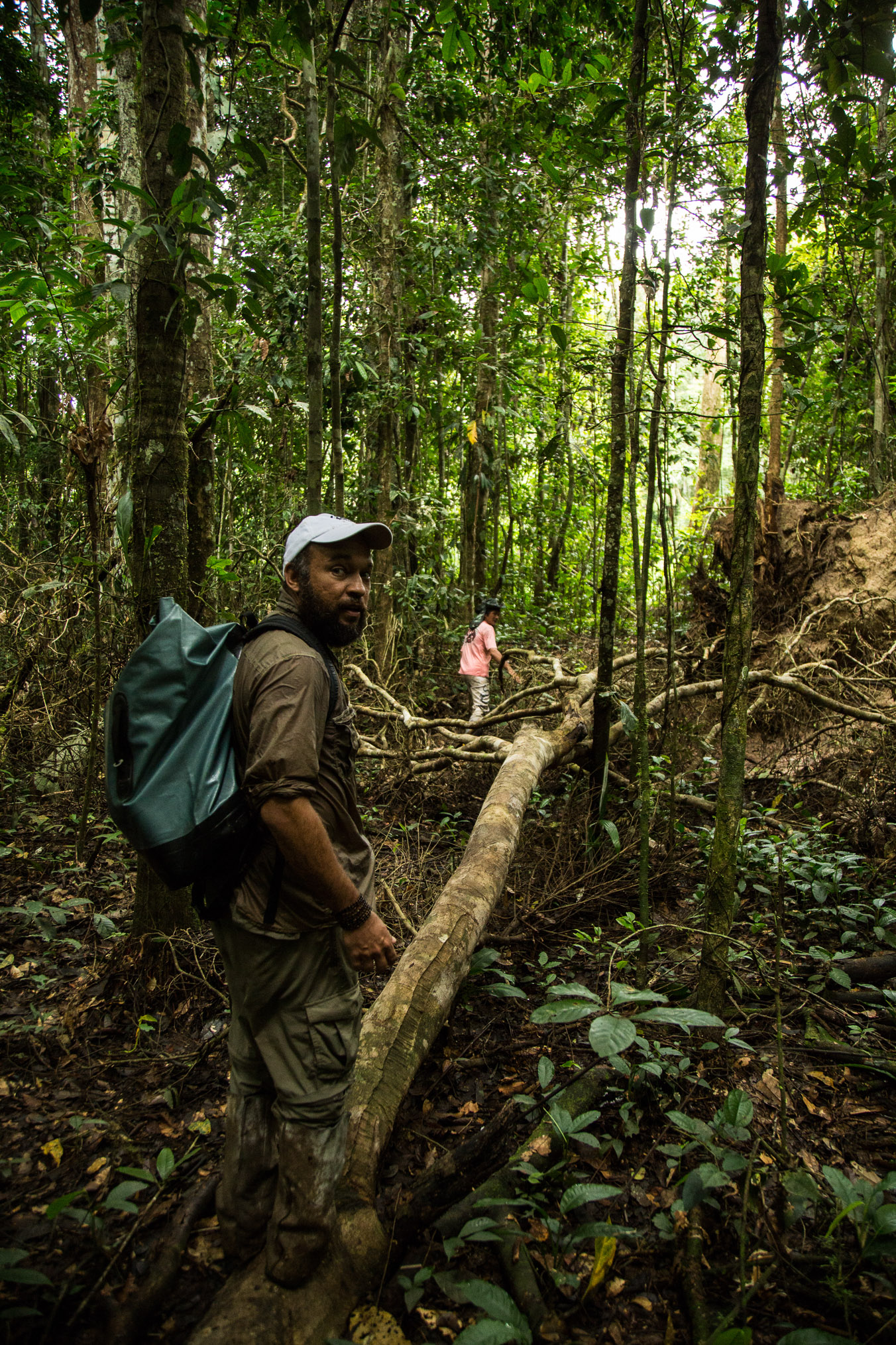 Brazilian primatologist Felipe Ennes follows a local guide down an overgrown trail to search for saki monkeys in the Amazon rainforest.