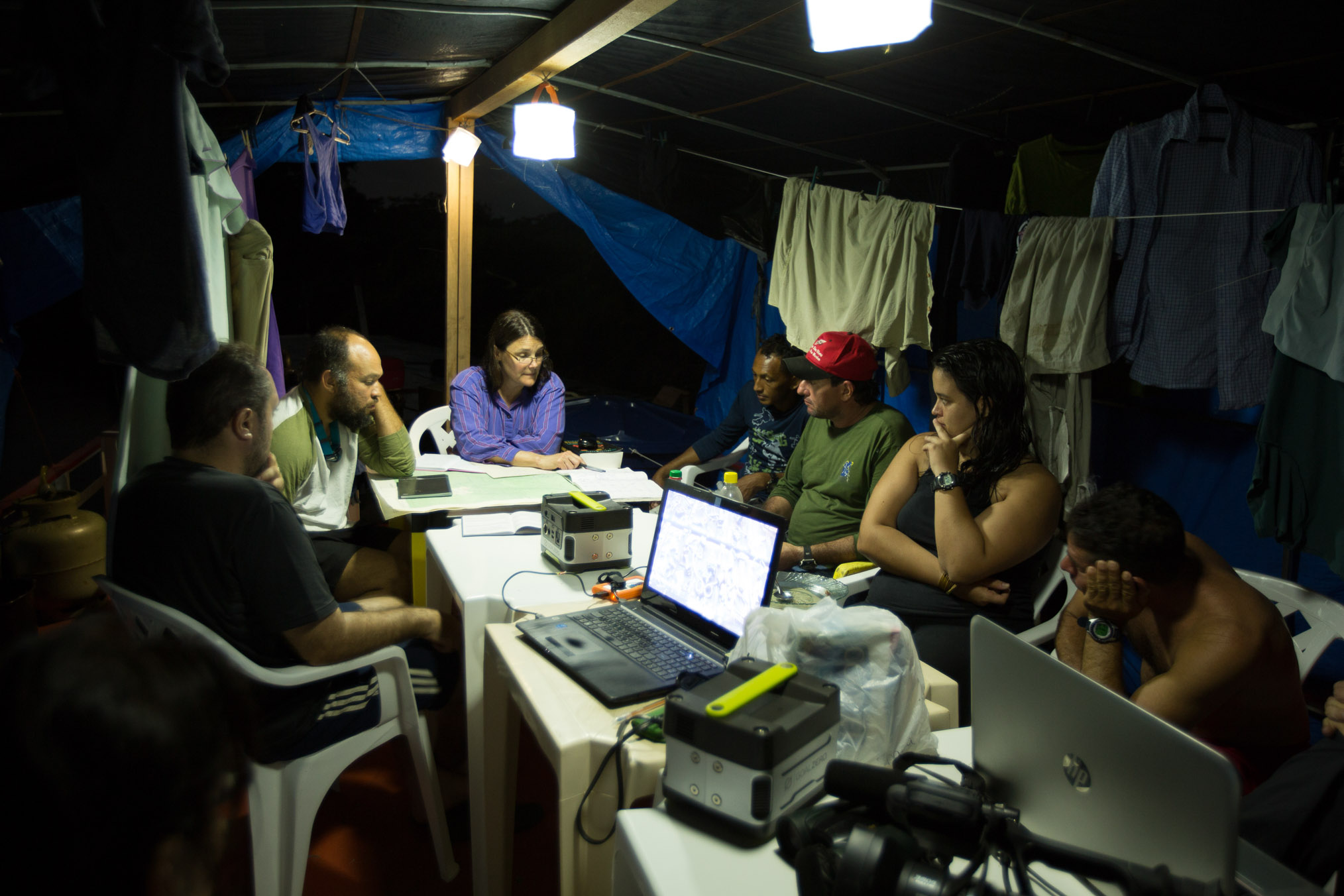 Surrounded by their drying laundry, the expedition team gathers for an evening meeting illuminated by solar lanterns on the second level of the houseboat.