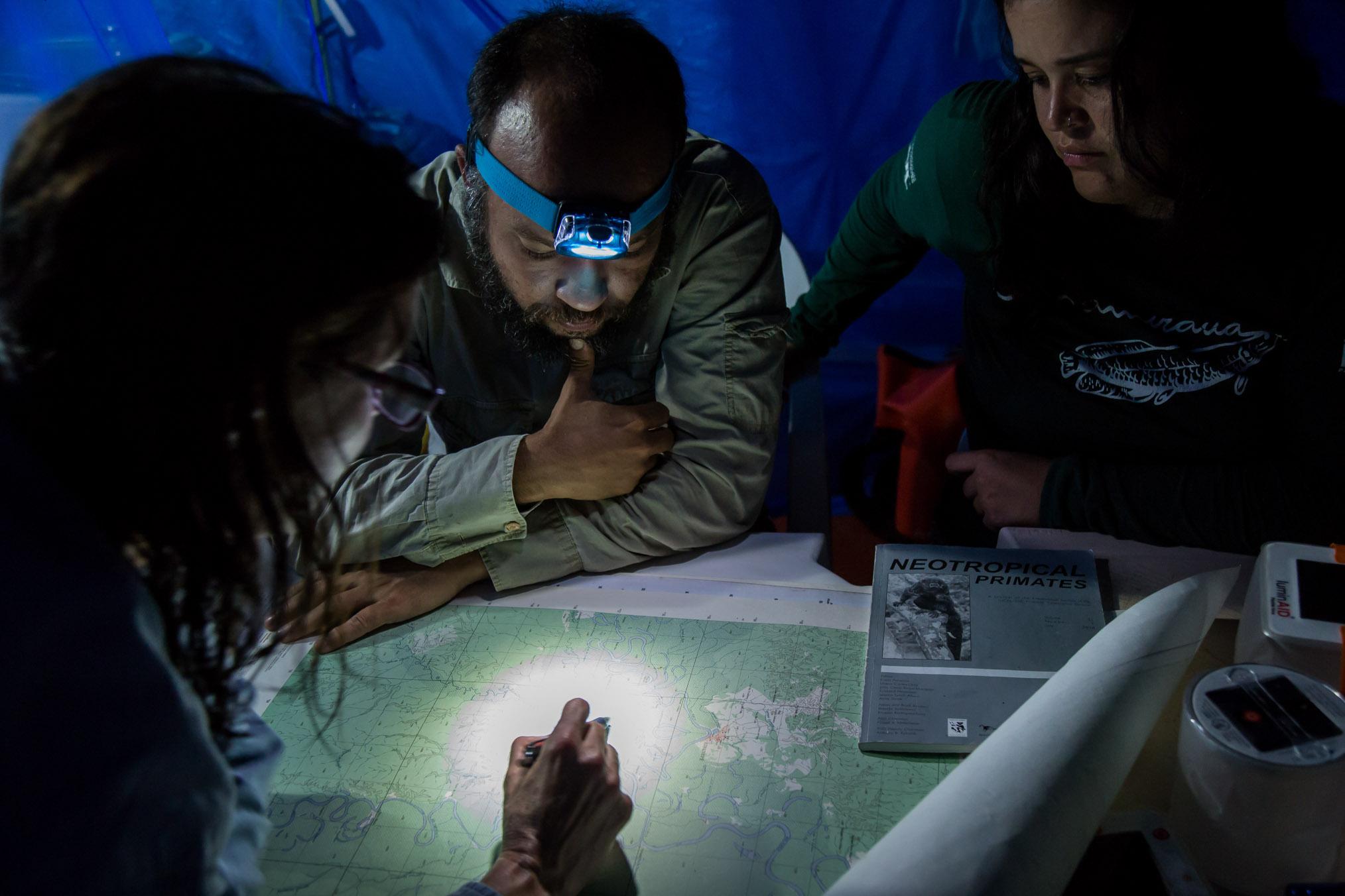 Scientists Laura Marsh (far left), Felipe Ennes, and Lísley Lemos study maps to determine the best areas to survey along the Eiru River.