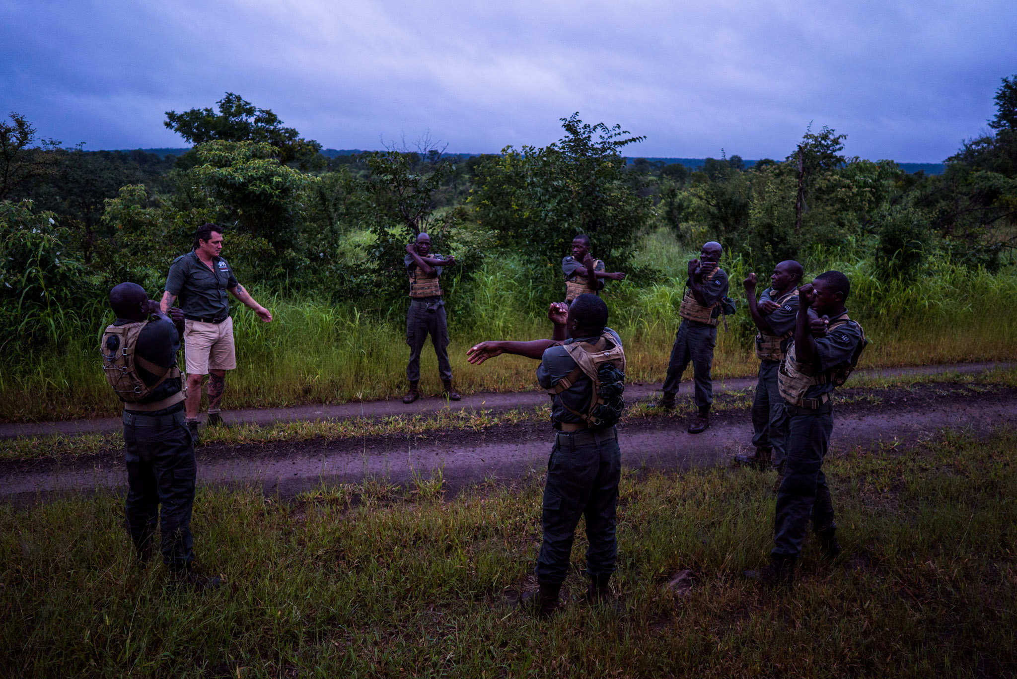Damien Mander and IAPF rangers warming up before morning training in Zimbabwe's Stanley and Livingstone Game Reserve—Photograph by Michael Hathorn, Ginkgo Agency