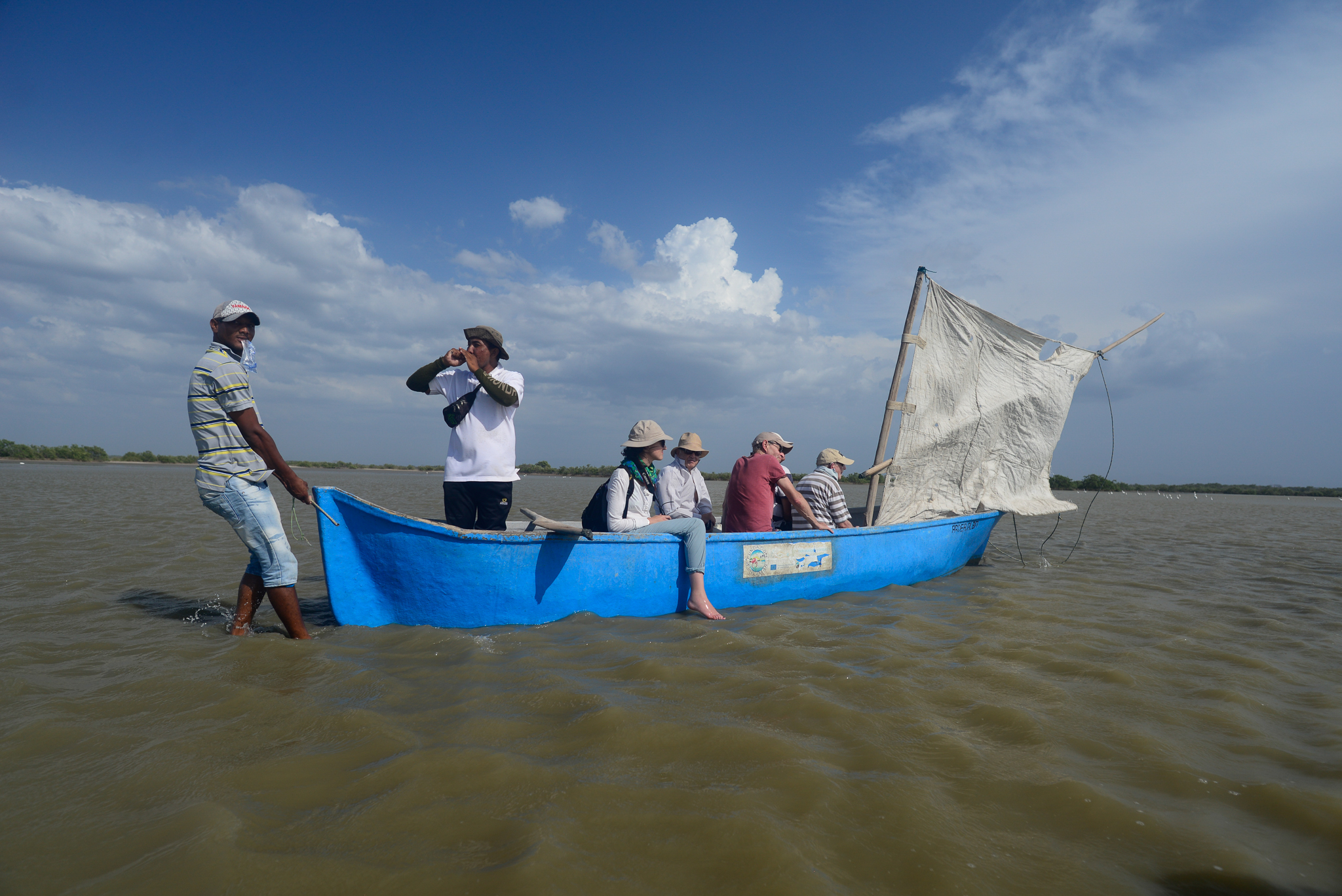 One Wayuú guide shouts instructions as another pulls a canoe of French tourists to shore in Los Flamencos Wildlife Reserve. Photograph by Lindsay Fendt