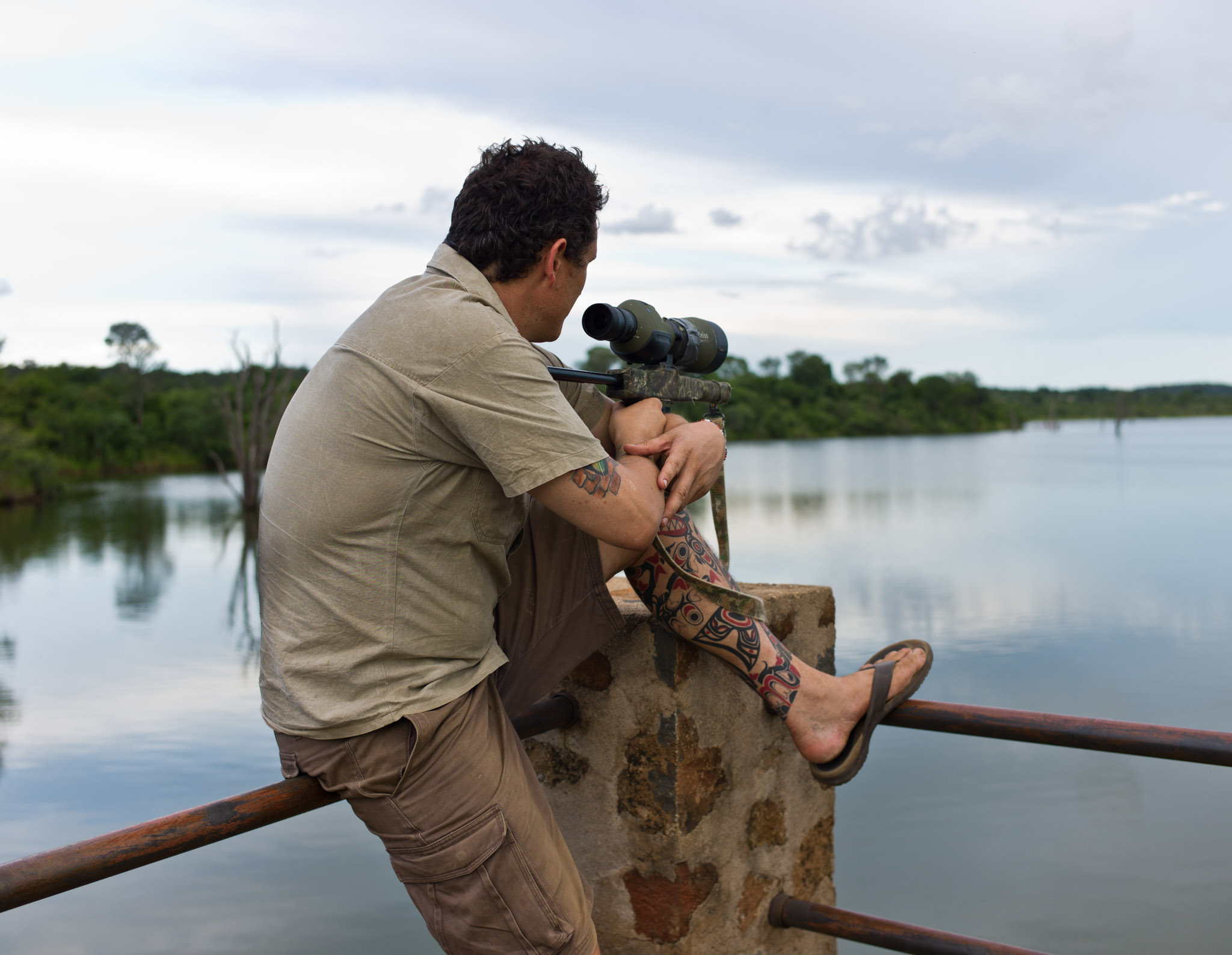 Damien Mander uses a spotting scope to keep watch over the Zimbabwe reserve he helps protect. Photograph by Erico Hiller