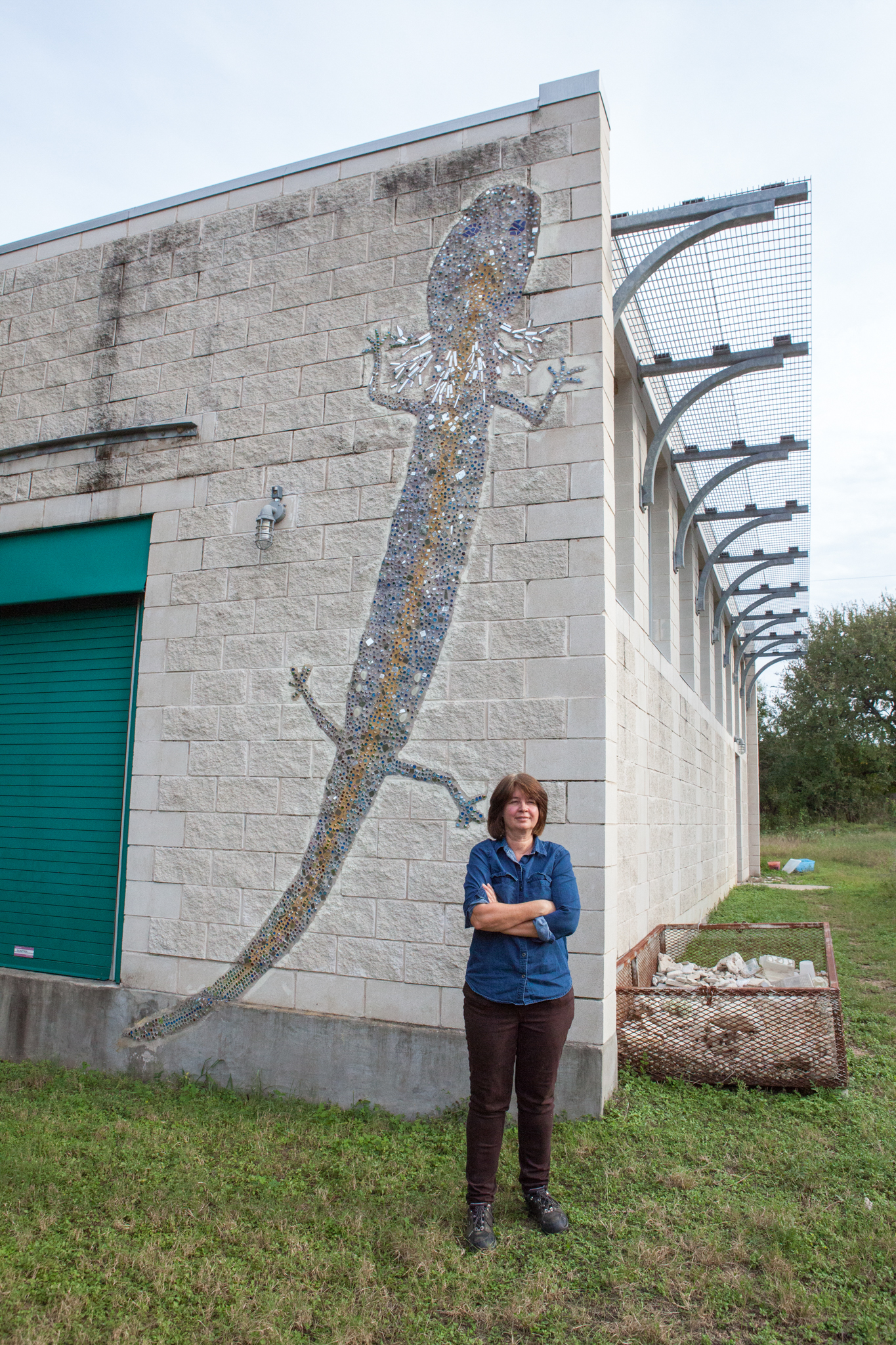 Dee Ann Chamberlain stands in front of the captive breeding facility building, well marked with a salamander mosaic. The breeding facility started out as three tanks that Chamberlain shared space with in her cubicle. There are now about 200 tanks housed in a dedicated building.