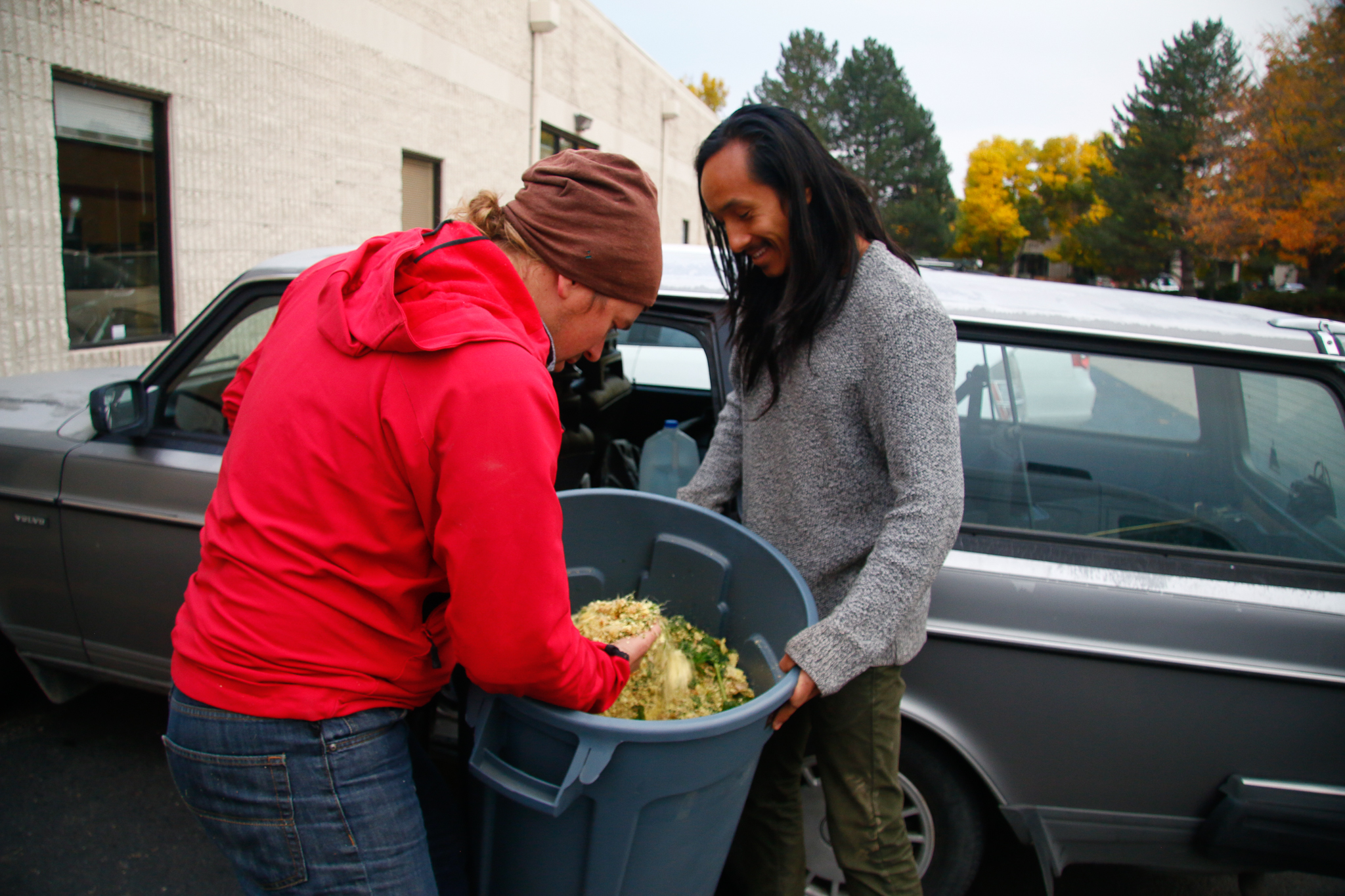 Xavier Rojas and Phil Taylor pick up a bin of ginger, parsley, and carrot shavings from Wonder Press juicers to feed to the bugs.