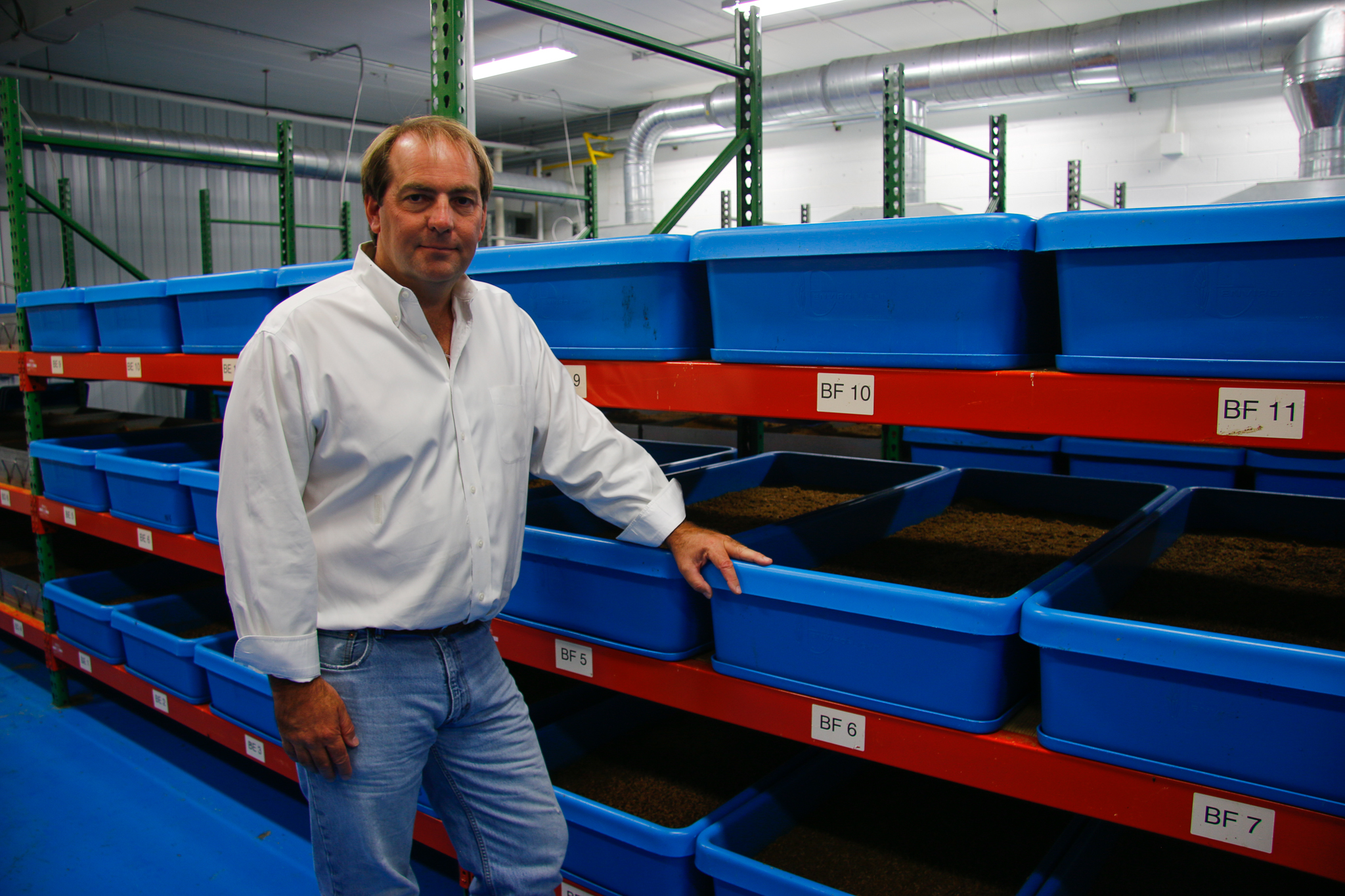 EnviroFlight CEO and founder Glen Courtright stands alongside bins of young larvae in his Ohio factory. In 2016, Courtirght's company was acquired by synthetic biology giant, Intrexon.