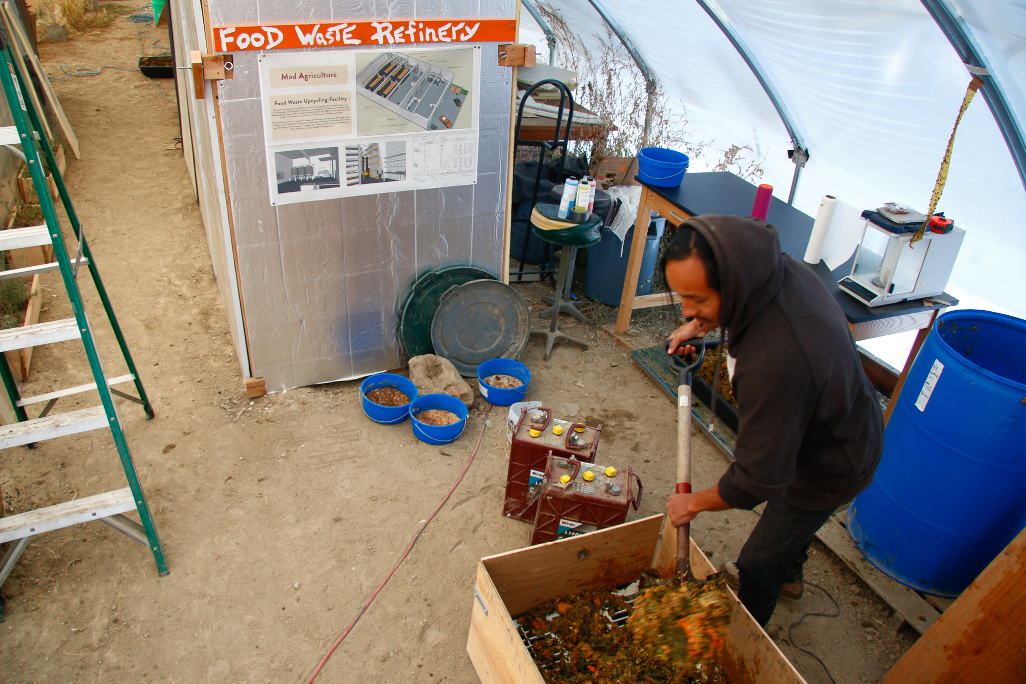 Xavier Rojas shovels fresh food waste from Wonder Press into fermentation barrels.