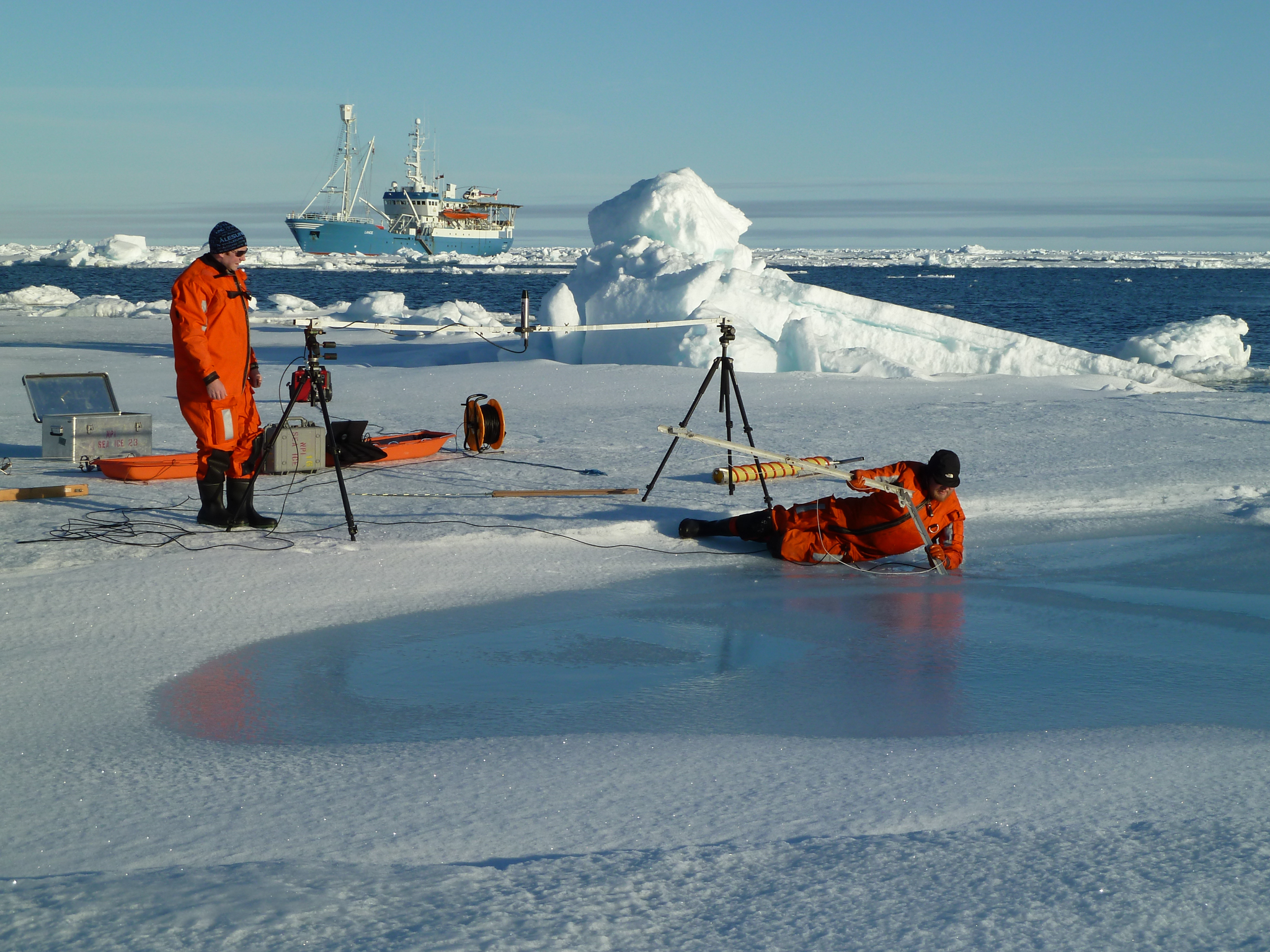 Researchers study melting ponds of various sizes and depths across the surface of the ice to better understand how the makeup of the surface affects reflection and absorption. Open water tends to absorb significantly more of the sun's energy, and ultimately accelerates the melting of surrounding sea ice. Photograph by Sebastian Gerland, Norwegian Polar Institute