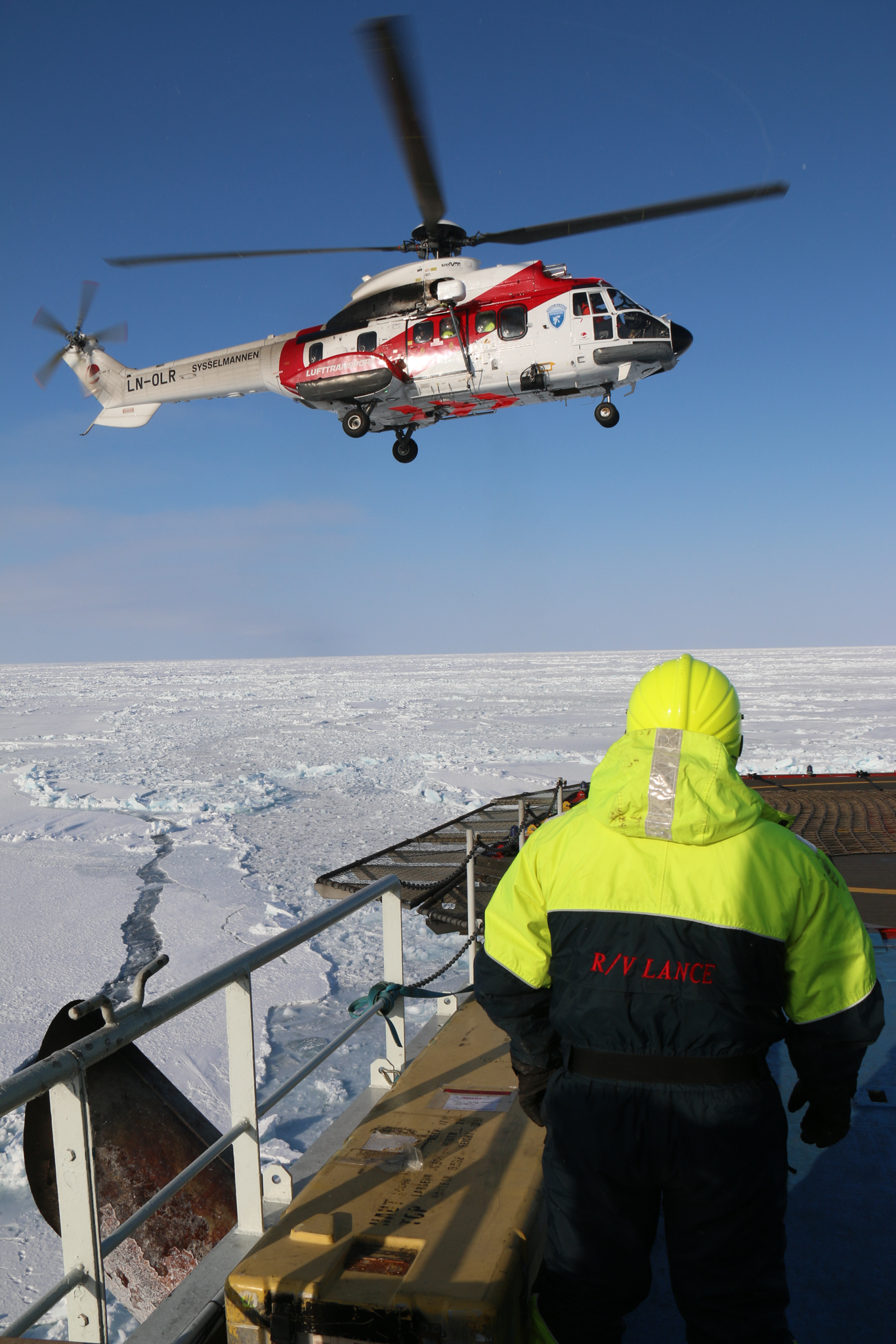 A helicopter transports expedition scientists from the ship to more remote field sites. Photograph by Mats Granskog, Norwegian Polar Institute