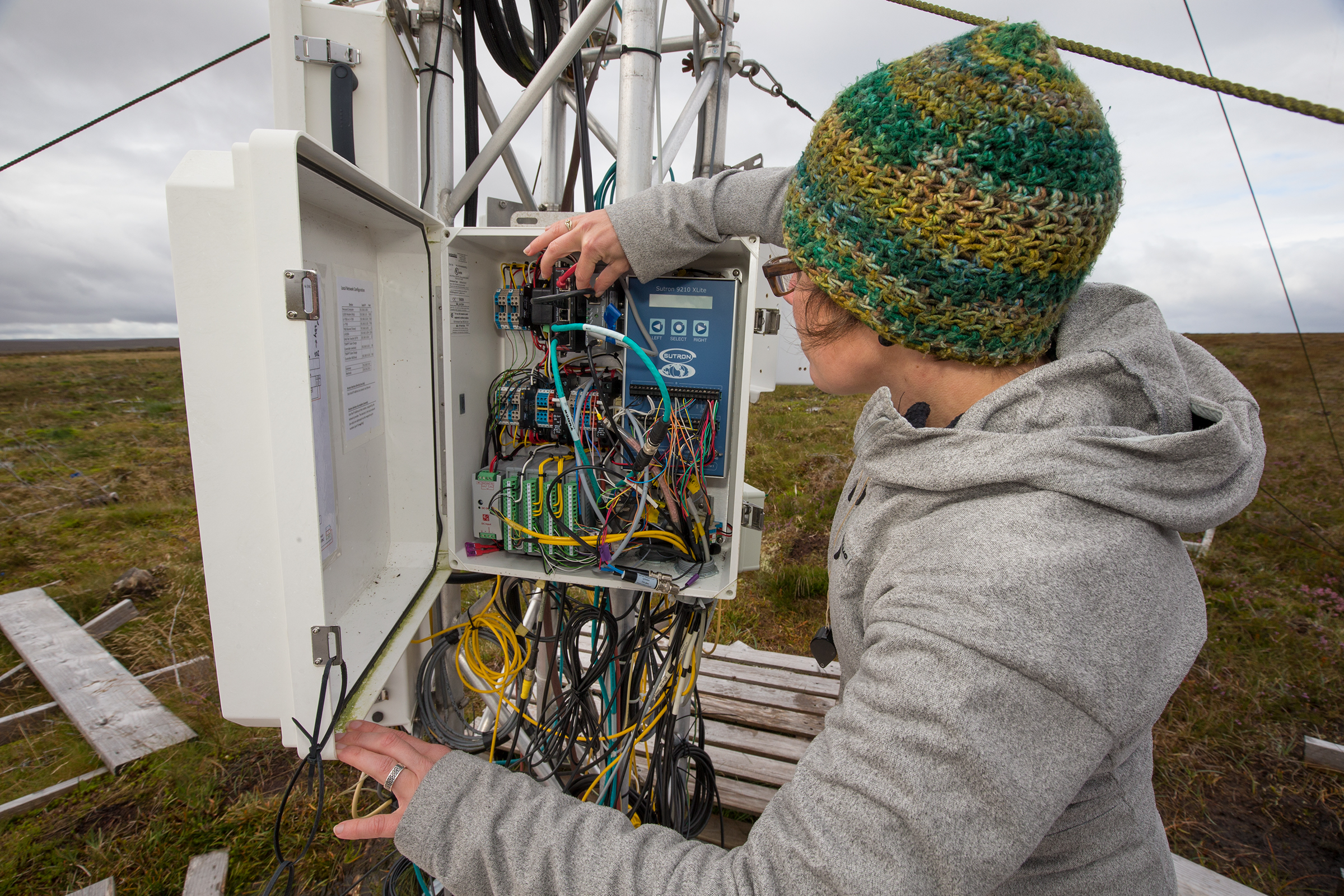 Scientist Roxanne Anderson checks the electronics of an eddy flux tower, an instrument that measures the level of CO2 in the air flowing over the bog in the Forsinard Flows Reserve.