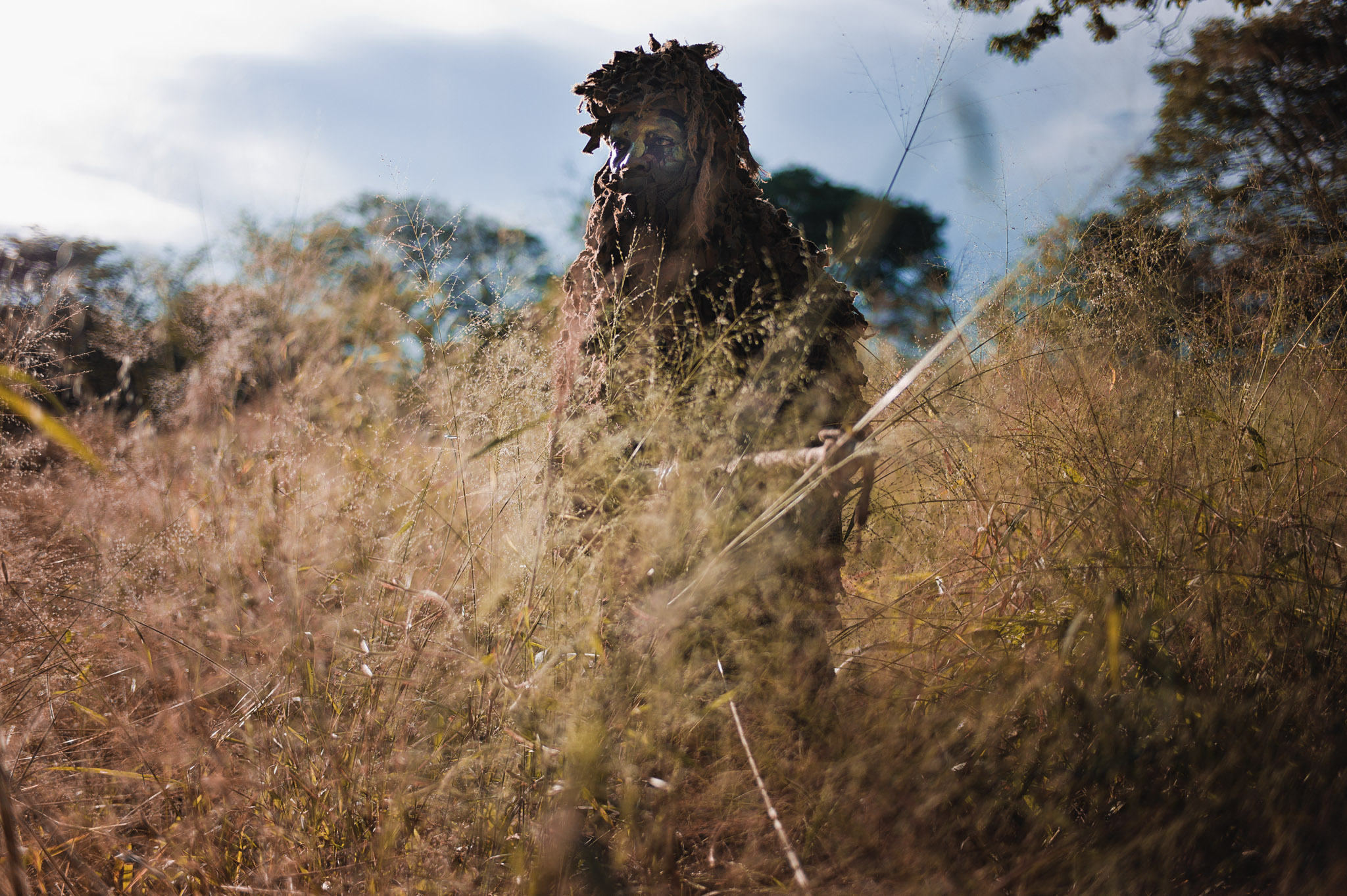 A ranger makes his way through the bush in a ghillie (sniper) suit, ever watchful for signs of poachers in the area. Photograph by Erico Hiller