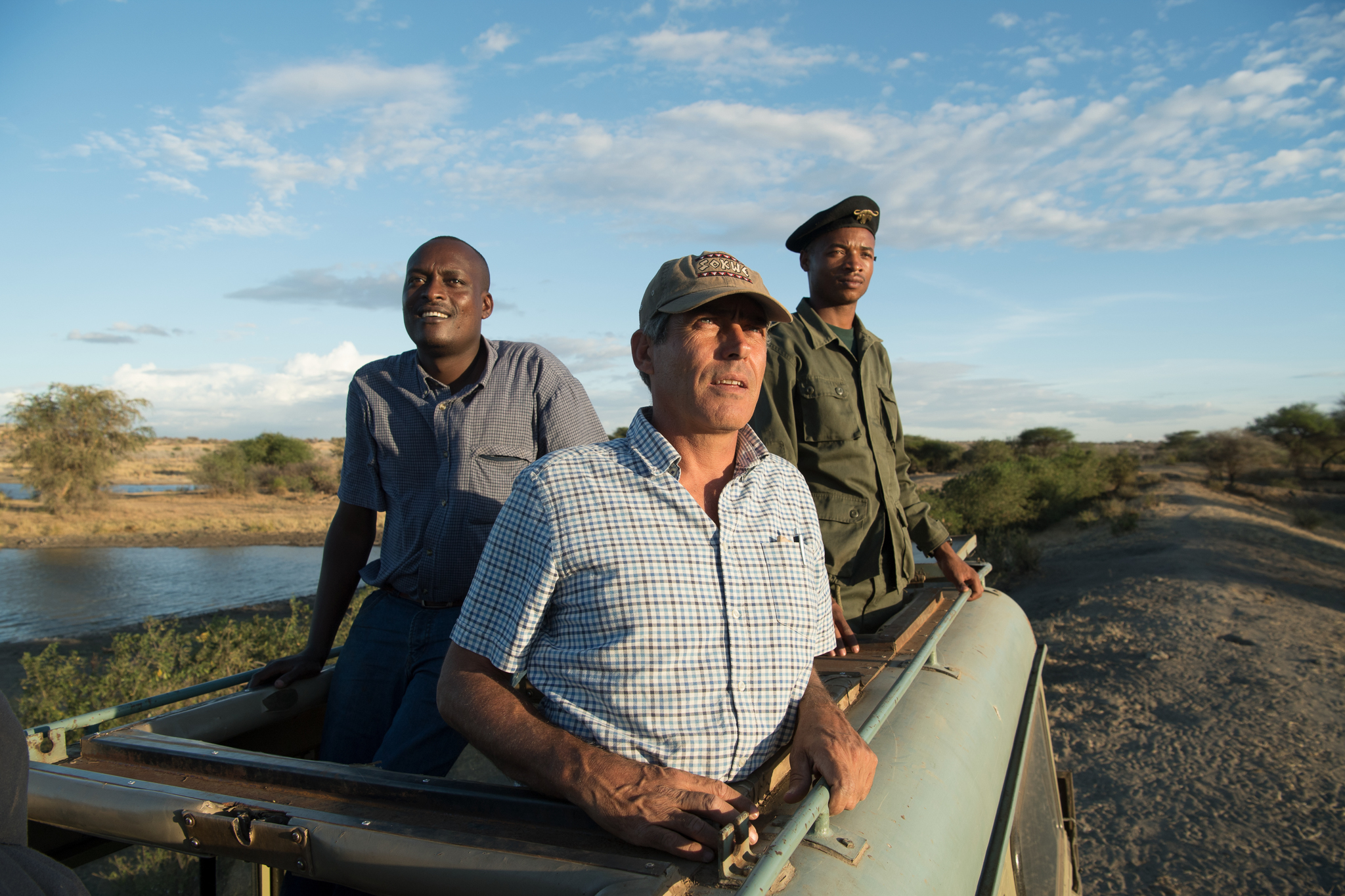 Damian Bell, Honeyguide's executive director (center), Leonard Charles (right), and Zungu Willy (left), watch elephants at Manyara Ranch, set against the towering backdrop of the Great Rift Valley escarpment.
