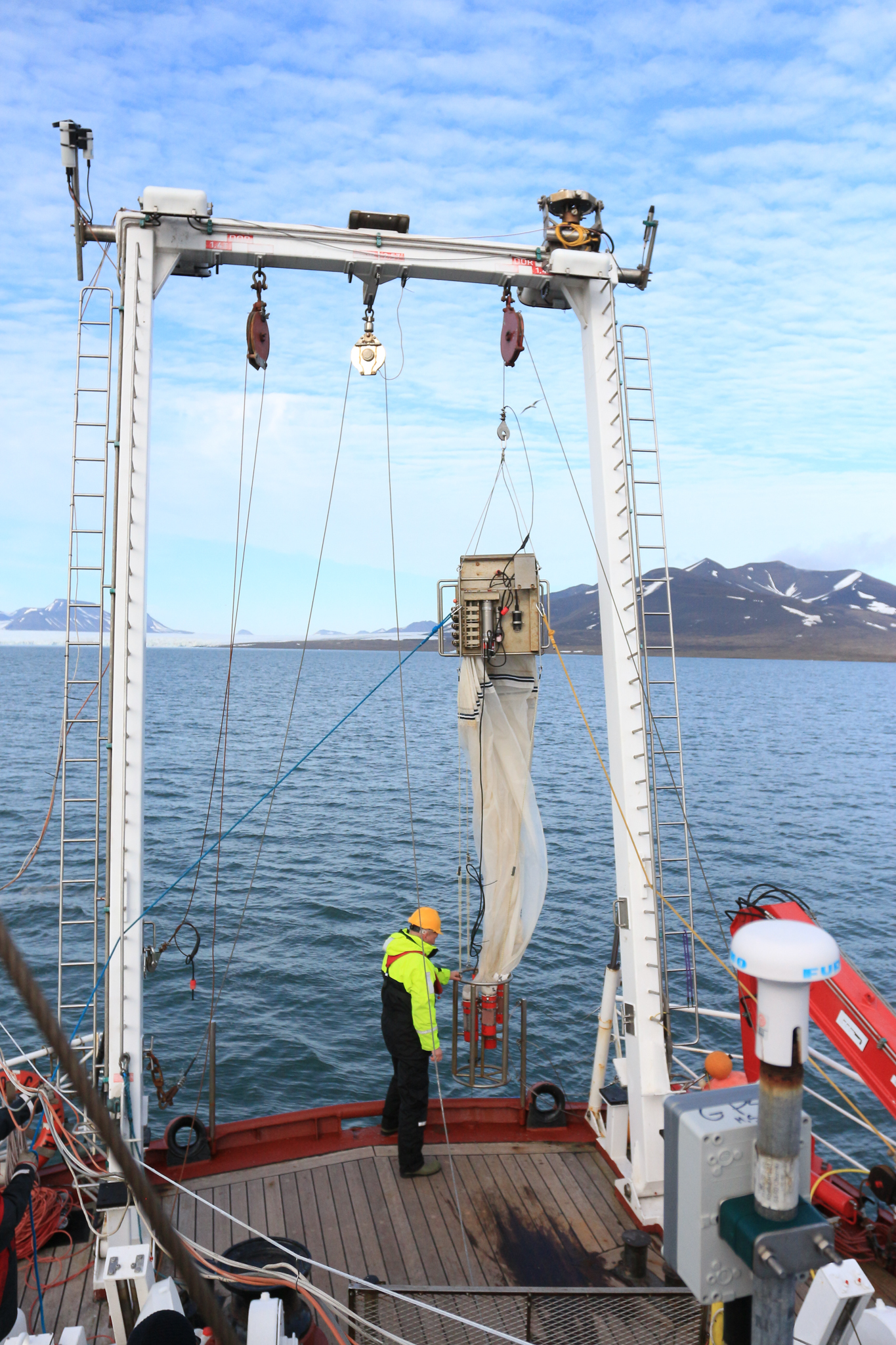 Scientists and crew lower the multinet into the ocean. The device opens and closes net bags at various depths so scientists can capture and study the organisms that live in different parts of the water column. Photograph by Hannah Hoag