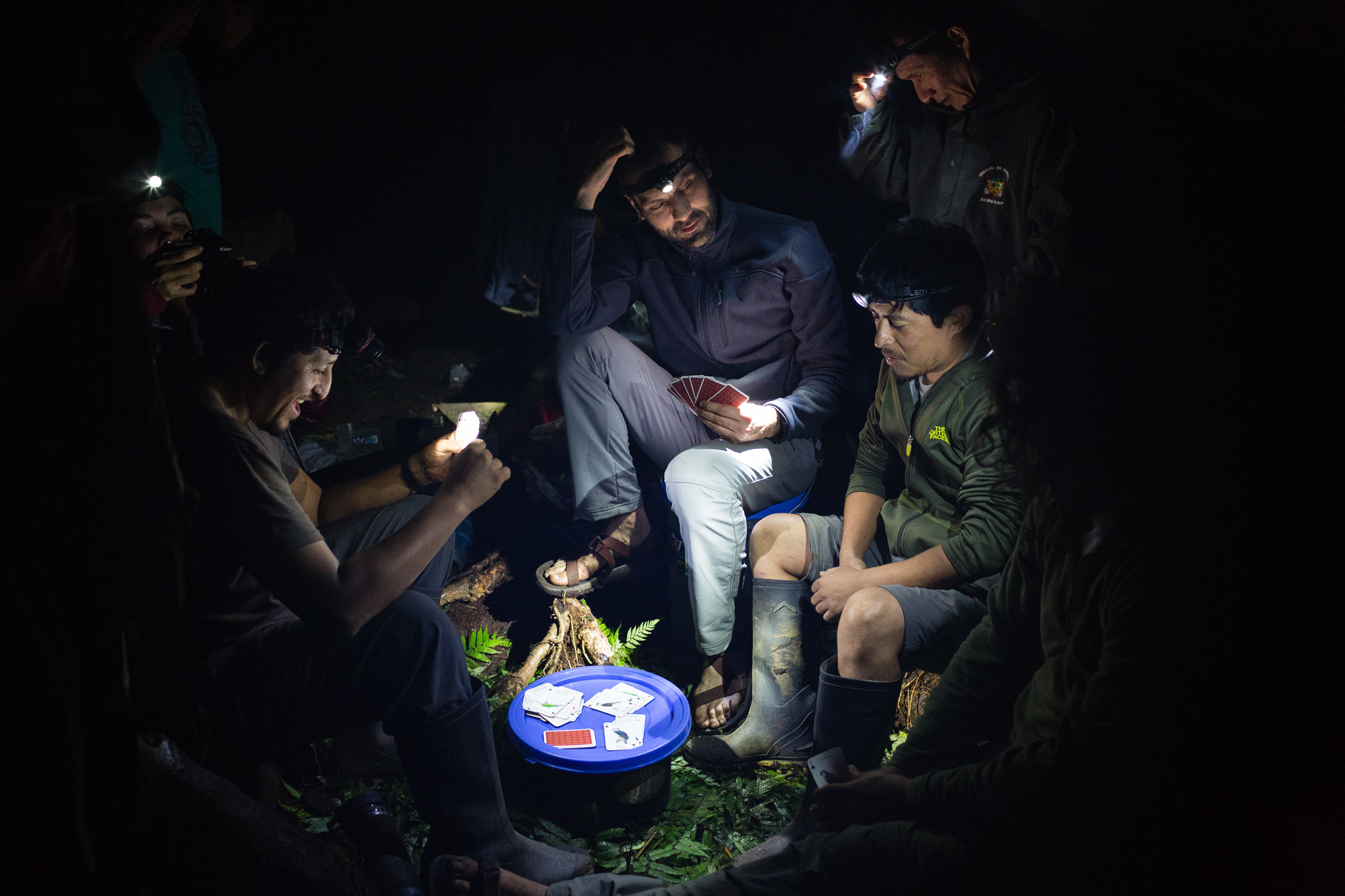 The team members entertain themselves over a game of cards illuminated by headlamp lights. Photo by Andy Isaacson