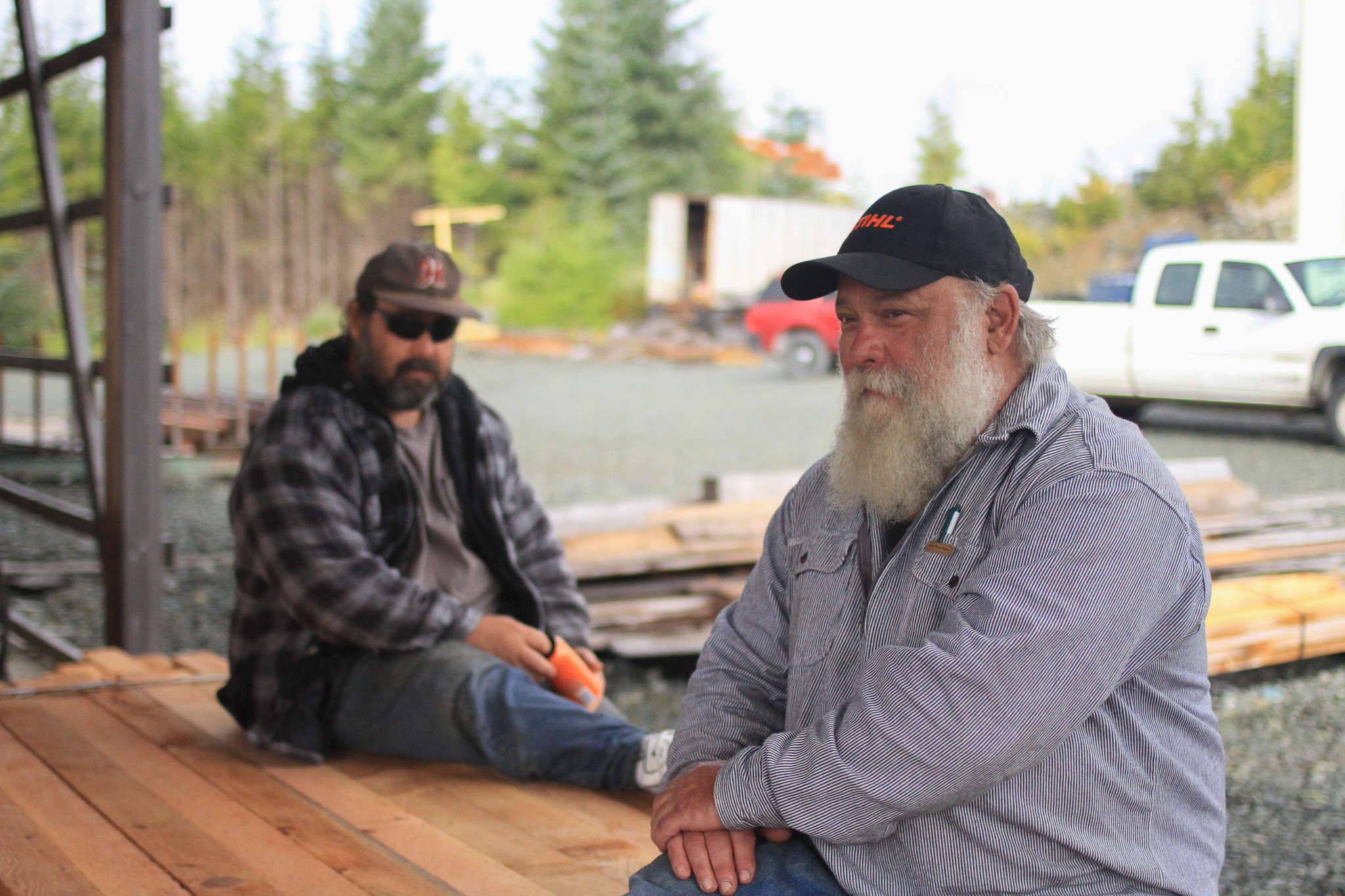 Hans Kohn (right) and his son Josh Kohn talk about young-growth prospects under an open air shelter shielding the mill's bandsaw and boards from Southeast Alaska's ever-present rain.