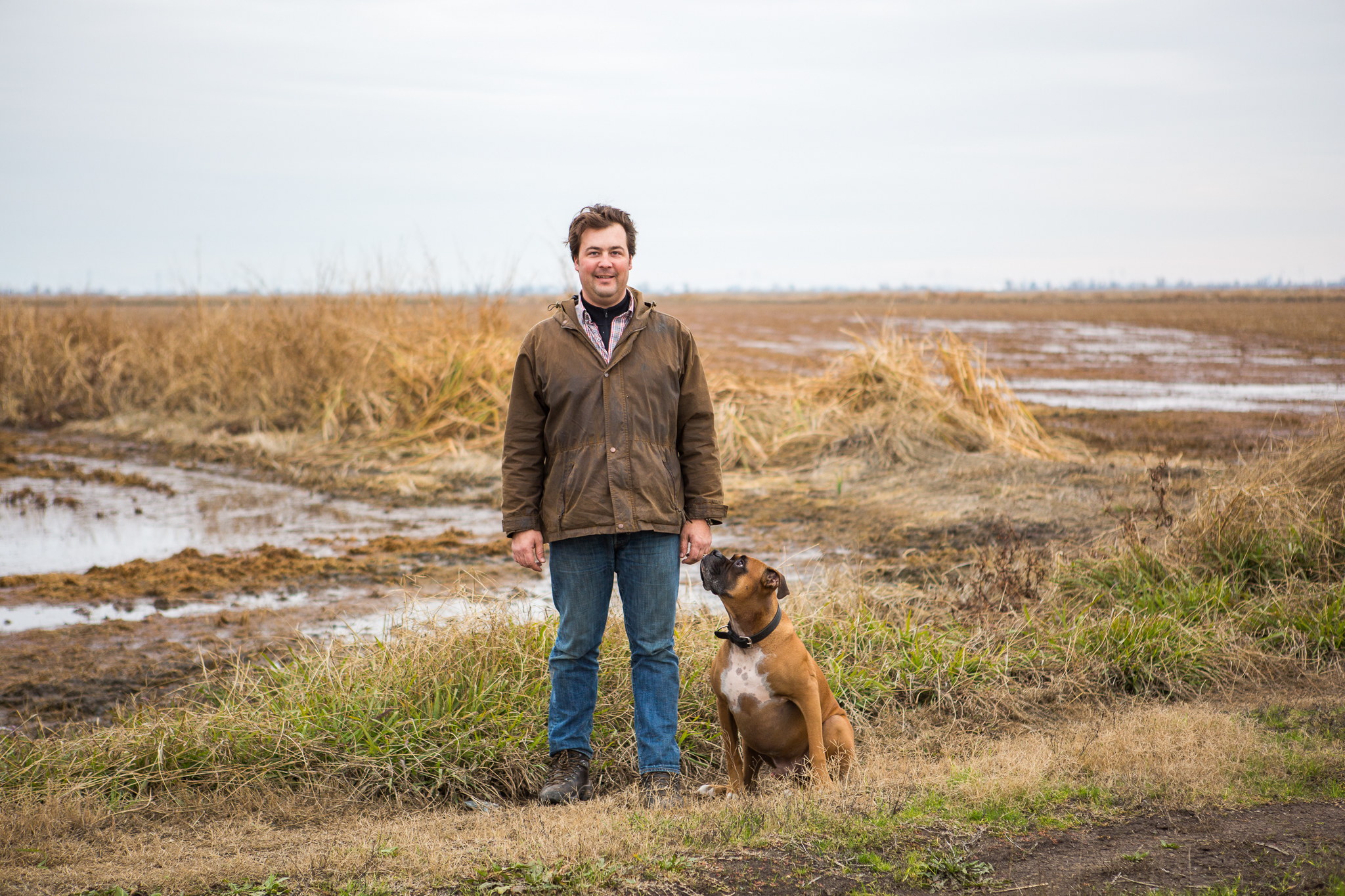 Dan Anderson, a fourth-generation rice farmer, stands next to his search-and-rescue dog, Cooper, in Richvale, California.