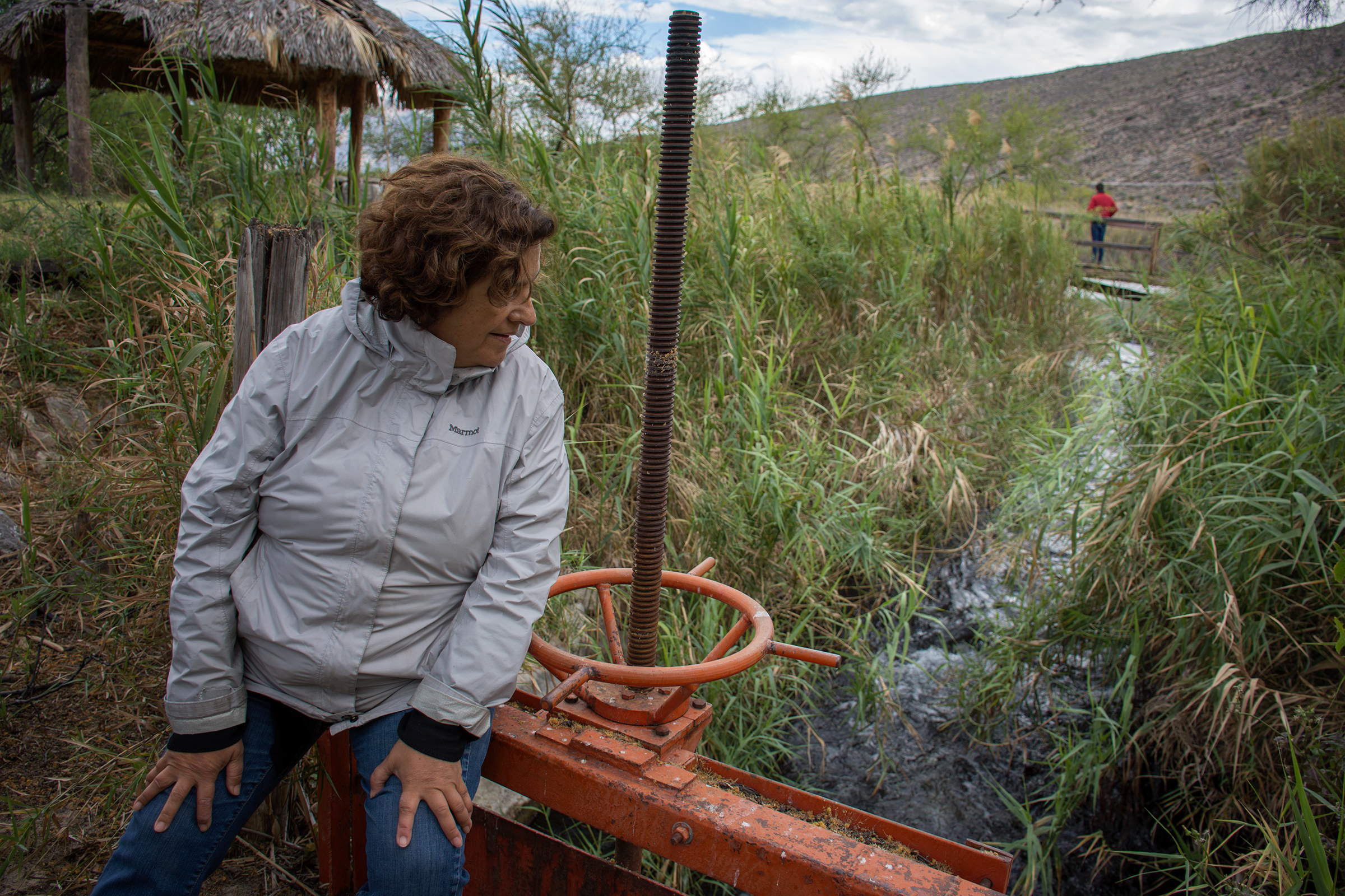 Microbiologist Valeria Souza leans against an open irrigation gate that is siphoning water from one of the remaining springs in the Cuatro Ciénegas basin.