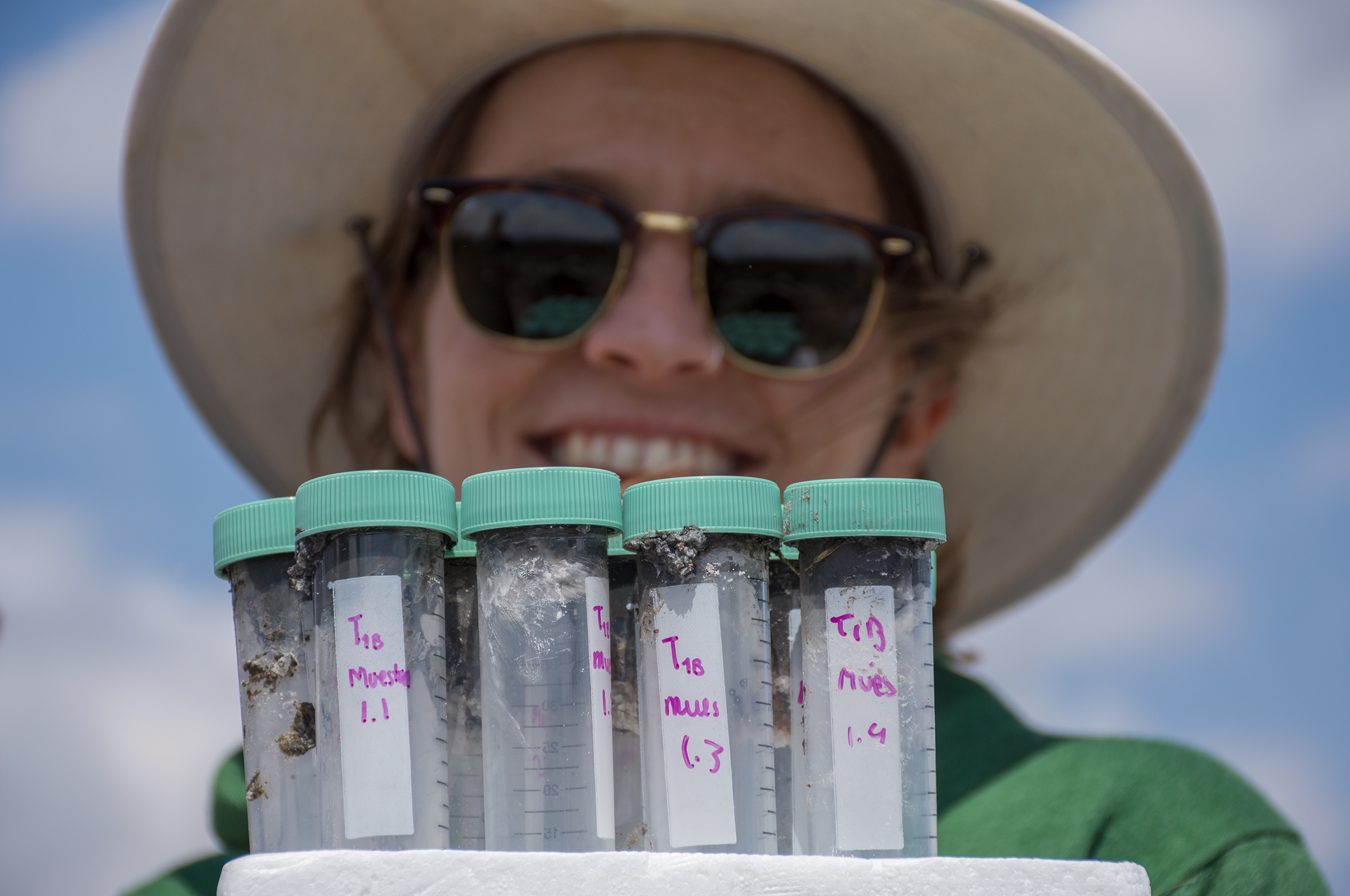 Elena Martin Clemente, a collaborating researcher from Spain, smiles behind vials that will help provide a measure of microbial biodiversity in the basin.