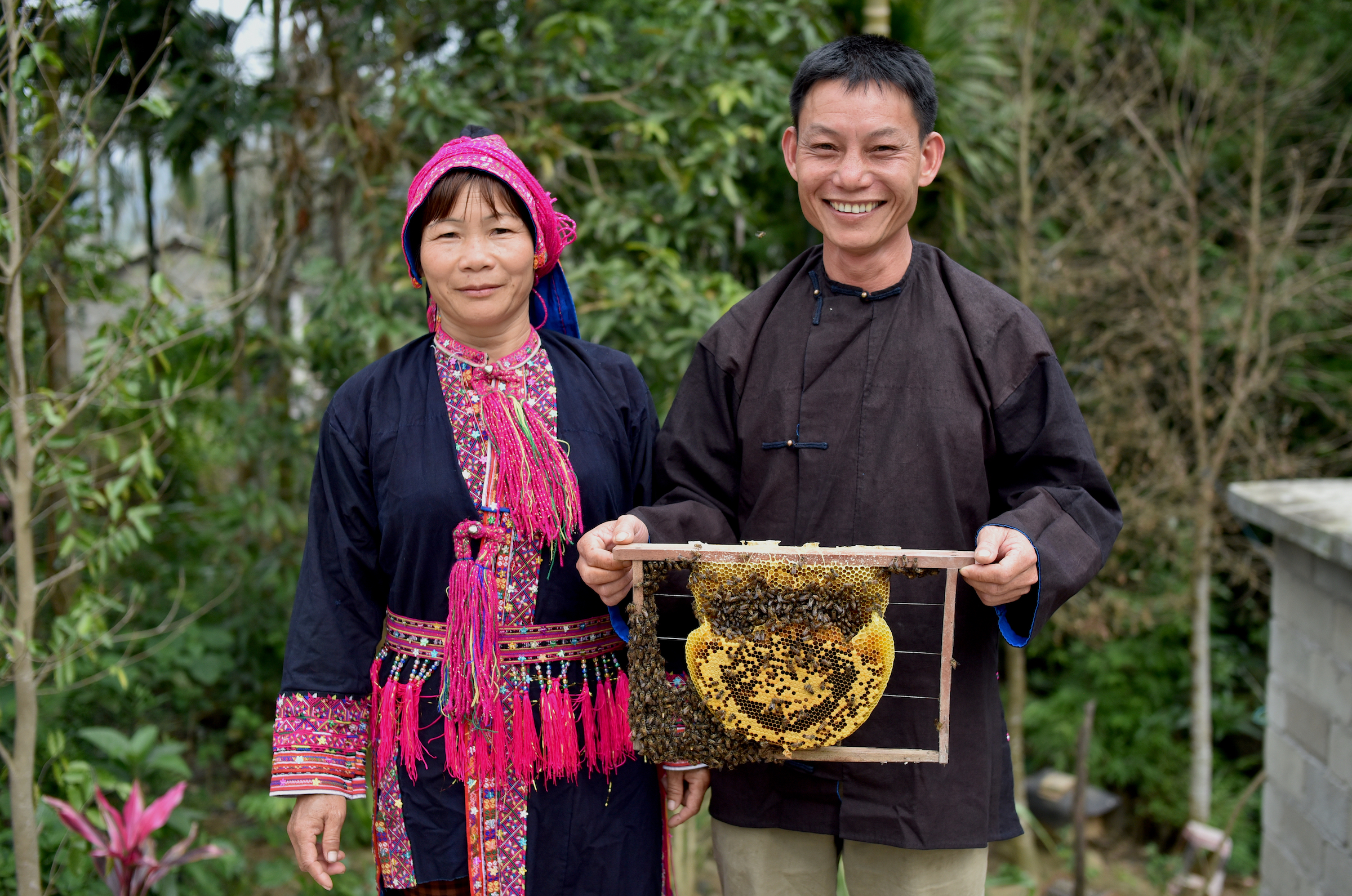 Li Wenyong and his wife Xiumei hold up a honeycomb from one of their hives. Conservationists hope that honey may provide a sustainable source of income for people in Hainan. Photograph courtesy of Kadoorie Farm & Botanic Garden