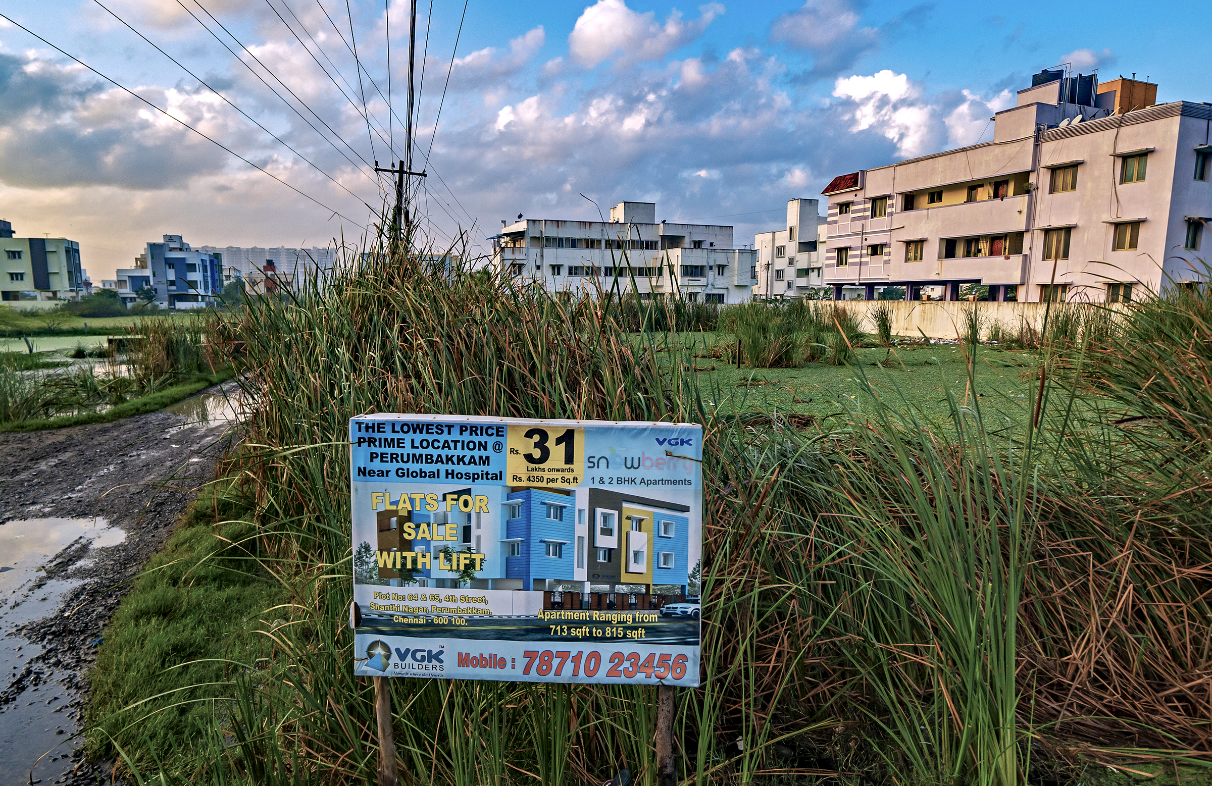 Chennai's marshlands continue to be paved over and sold, despite urban development's impacts on the floods, droughts, and the region's dwindling wetland ecosystems. This sign advertises prime real estate locations at Perumbakken, a once-expansive wetland in Chennai.
