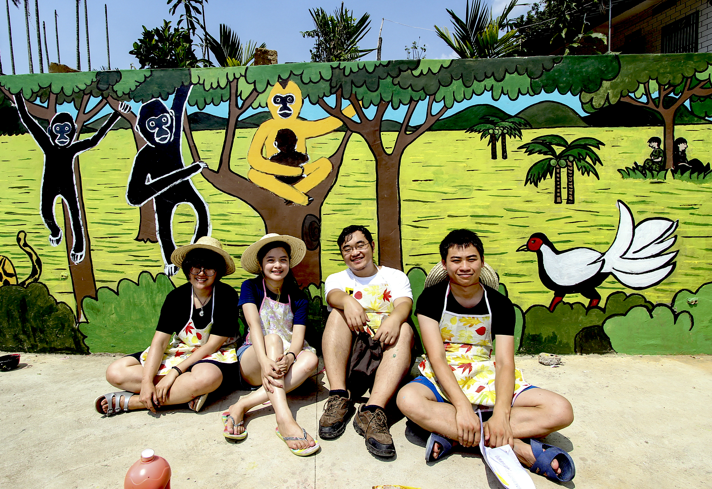Students sit in front of a new mural of Hainan gibbons in the village of Miao Cun. The mural was painted as part of Kadoorie Farm's campaign to raise awareness about the Hainan gibbon. Photograph courtesy of Kadoorie Farm & Botanic Garden