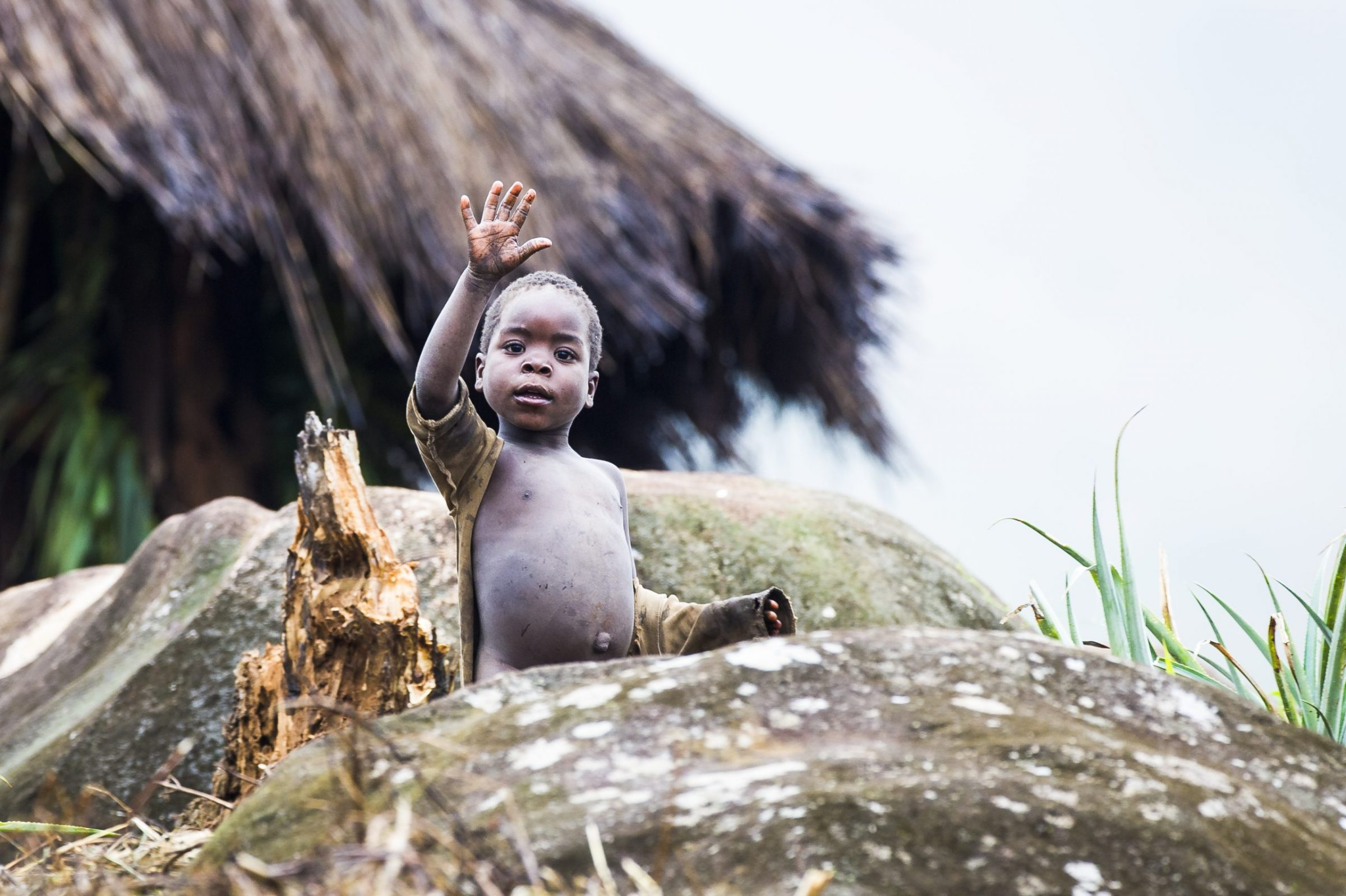 A young Mozambican child waves from outside his home.