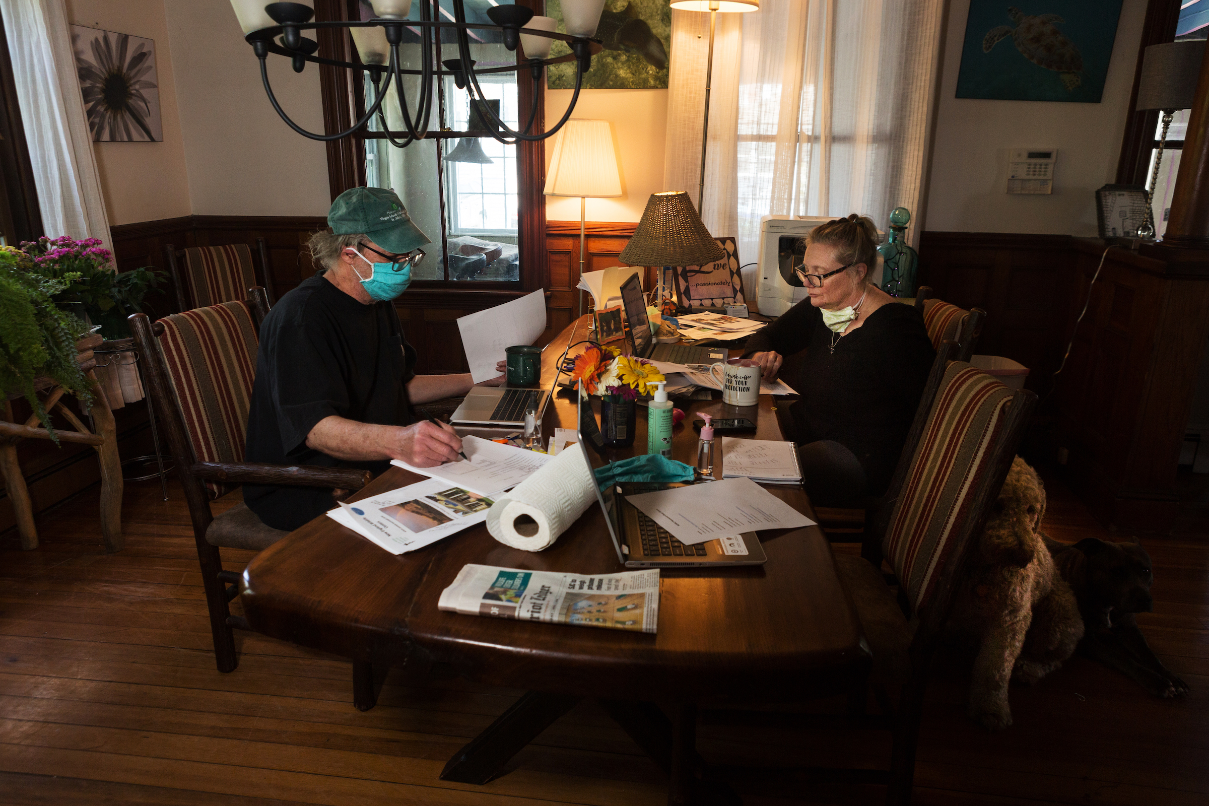 Dr. Greg Mertz (left) of the New England Wildlife Center and Katrina Bergman (right) work at the table in their home in Hull, Massachusetts. Mertz and Bergman are working on a bill that would allow veterinarians and licensed rehabilitators to use telehealth technologies to help diagnose wild animals.