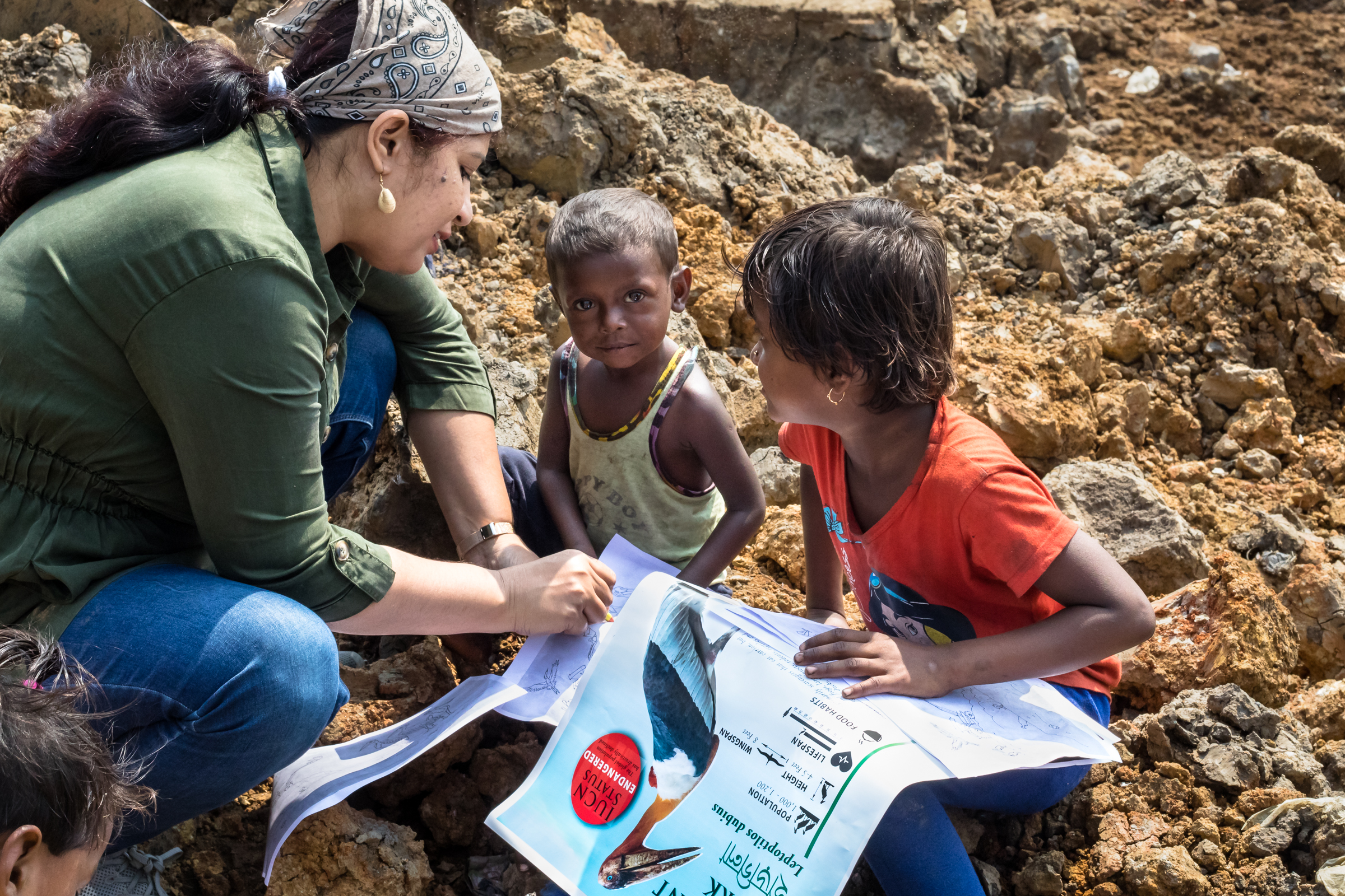 Purnima Devi Barman presents informational posters, coloring pages, and food to the people living and working in the sprawling landfill with the goal of raising awareness for the greater adjutants.