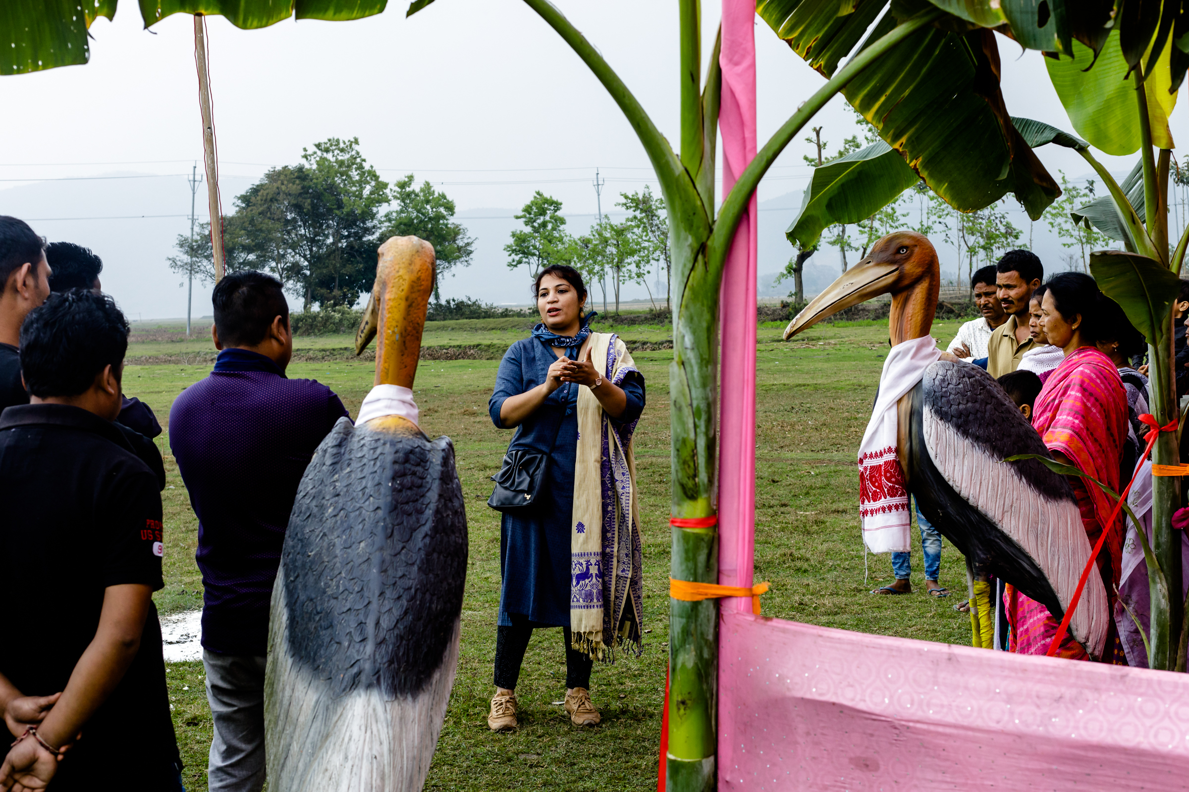 "Biologist Purnima Devi Barman is pictured speaking to villagers and members of the ""Hargila Army"" at a cricket match organized to raise awareness and educate locals about greater adjutant conservation efforts."