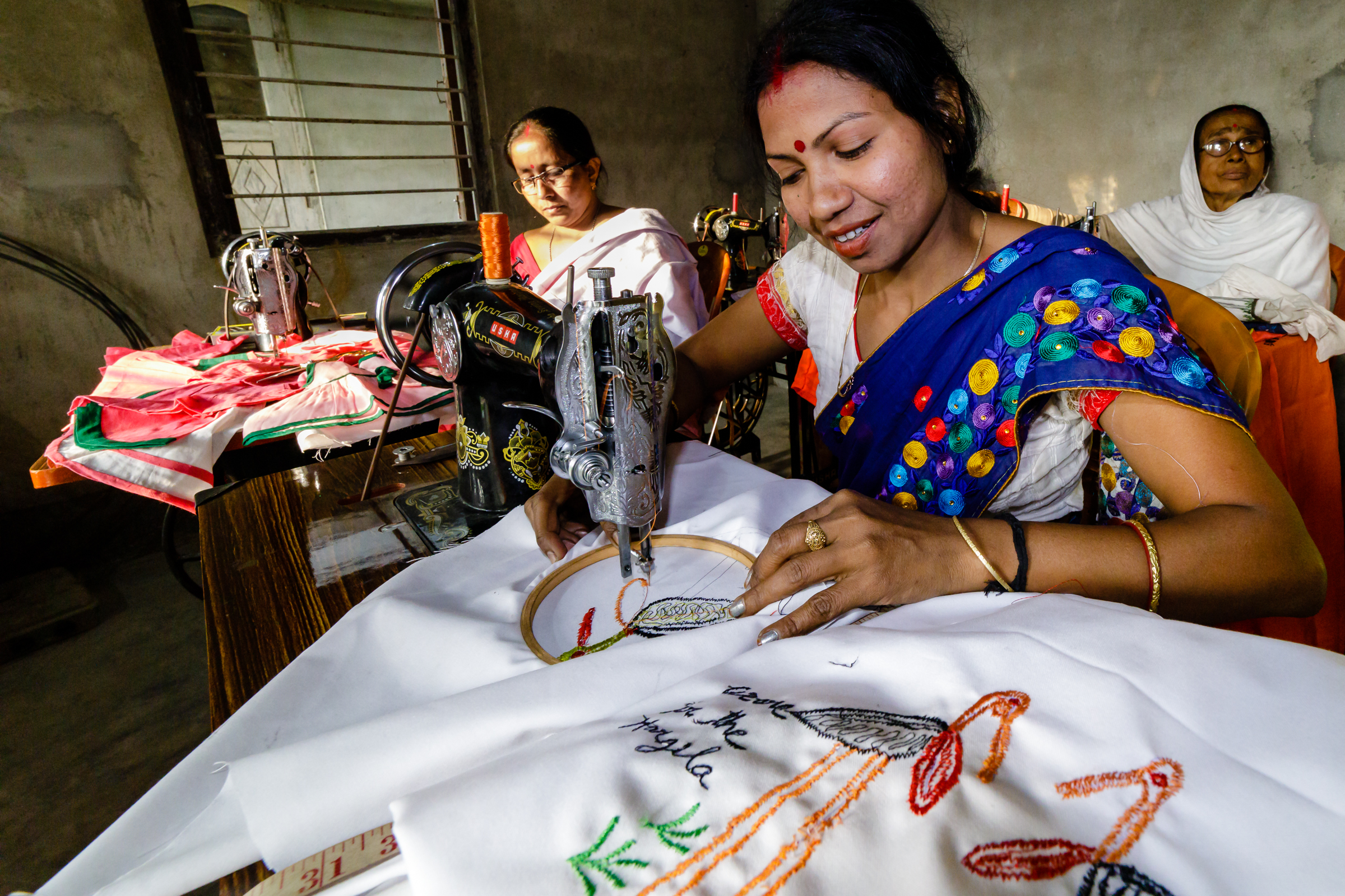 "Jonali, a member of the ""Hargila Army,"" is pictured sewing a tote bag with an embroidered greater adjutant motif to help combat plastic bag usage. Members of the Hargila Army take great pride in protecting this endangered species."