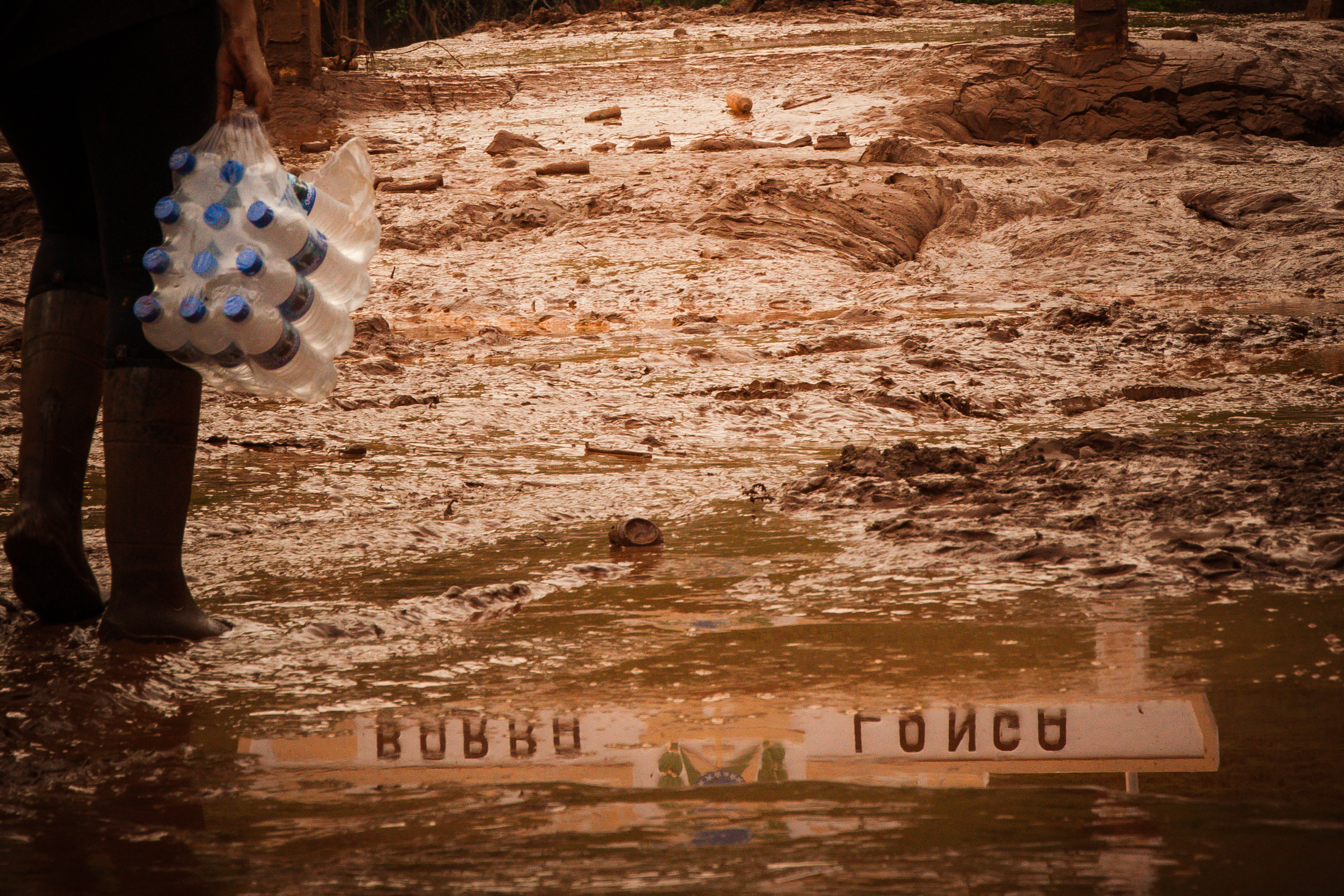 A resident of Barra Longa City carries water down a muddy street days after a tailings dam ruptured, killing 19 people and destroying the Doce River.